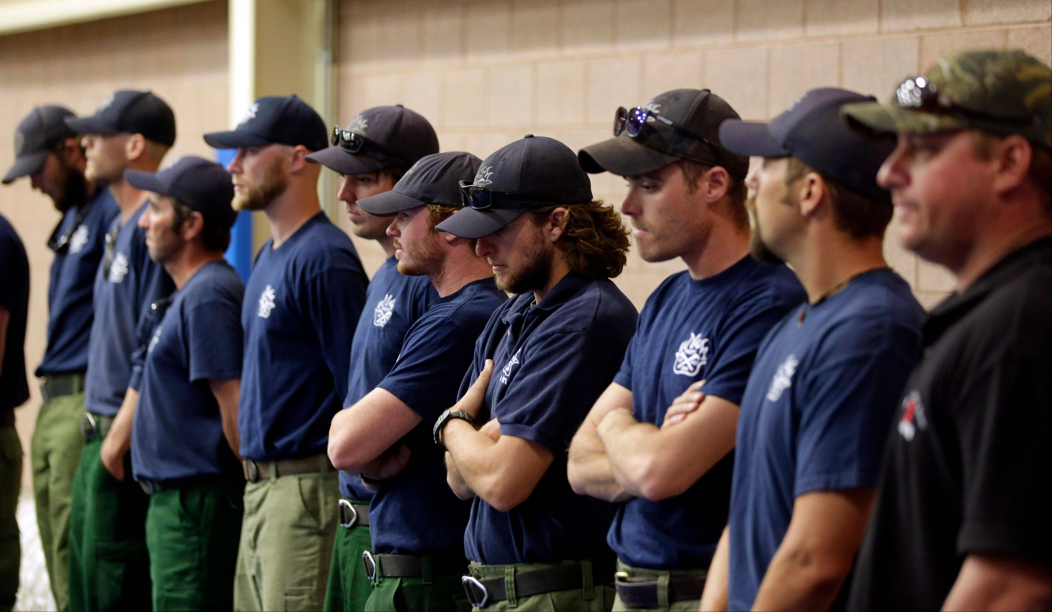 Firefighters wait to go inside for a memorial service in Prescott, Ariz., Monday, July 1, 2013. The firefighters were honoring 19 Granite Mountain Hotshot firefighters who were killed while battling an out-of-control wildfire near Yarnell, Ariz., on Sunday.