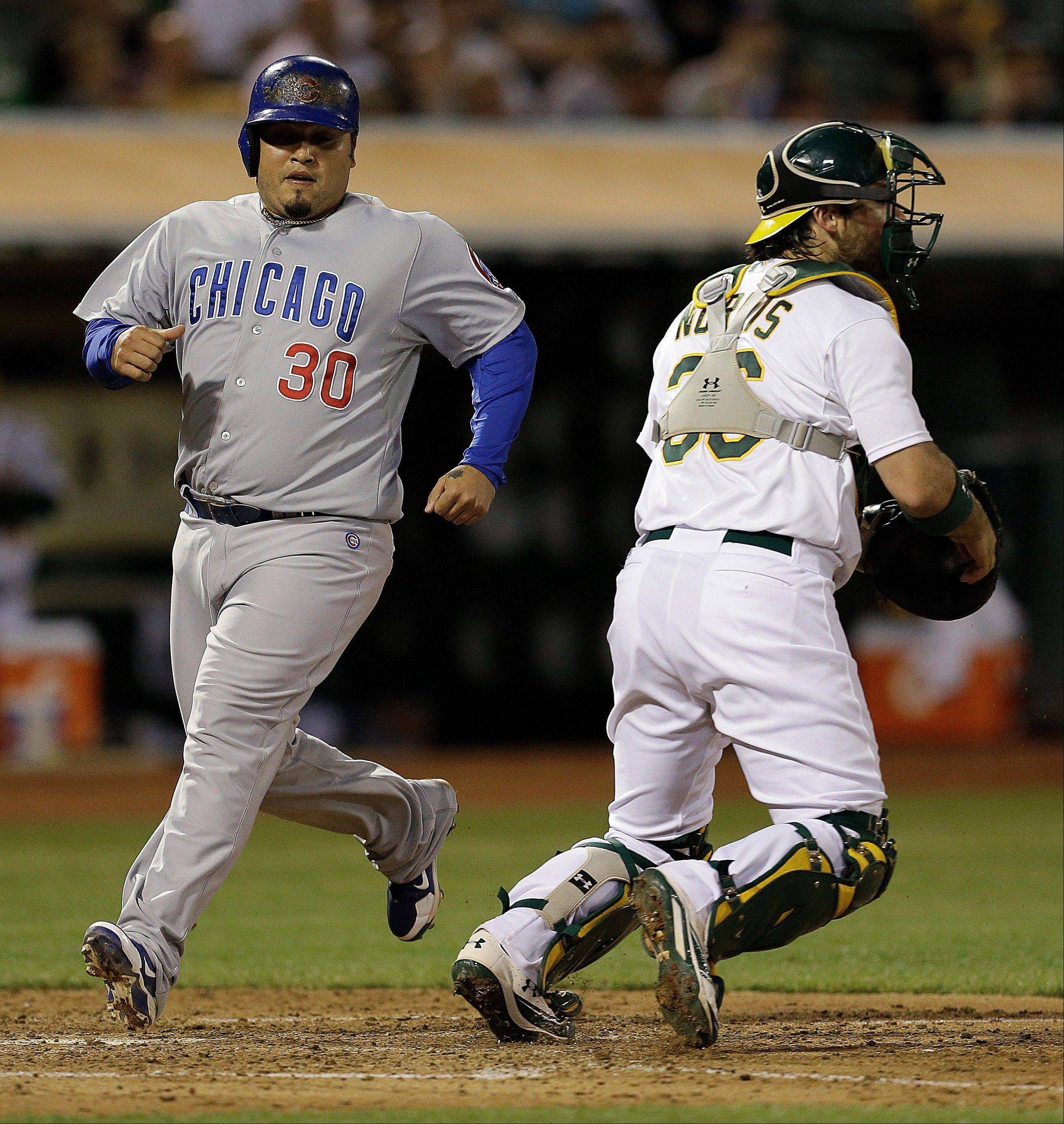The Cubs' Dioner Navarro scores past Athletics catcher Derek Norris in the sixth inning Tuesday in Oakland.