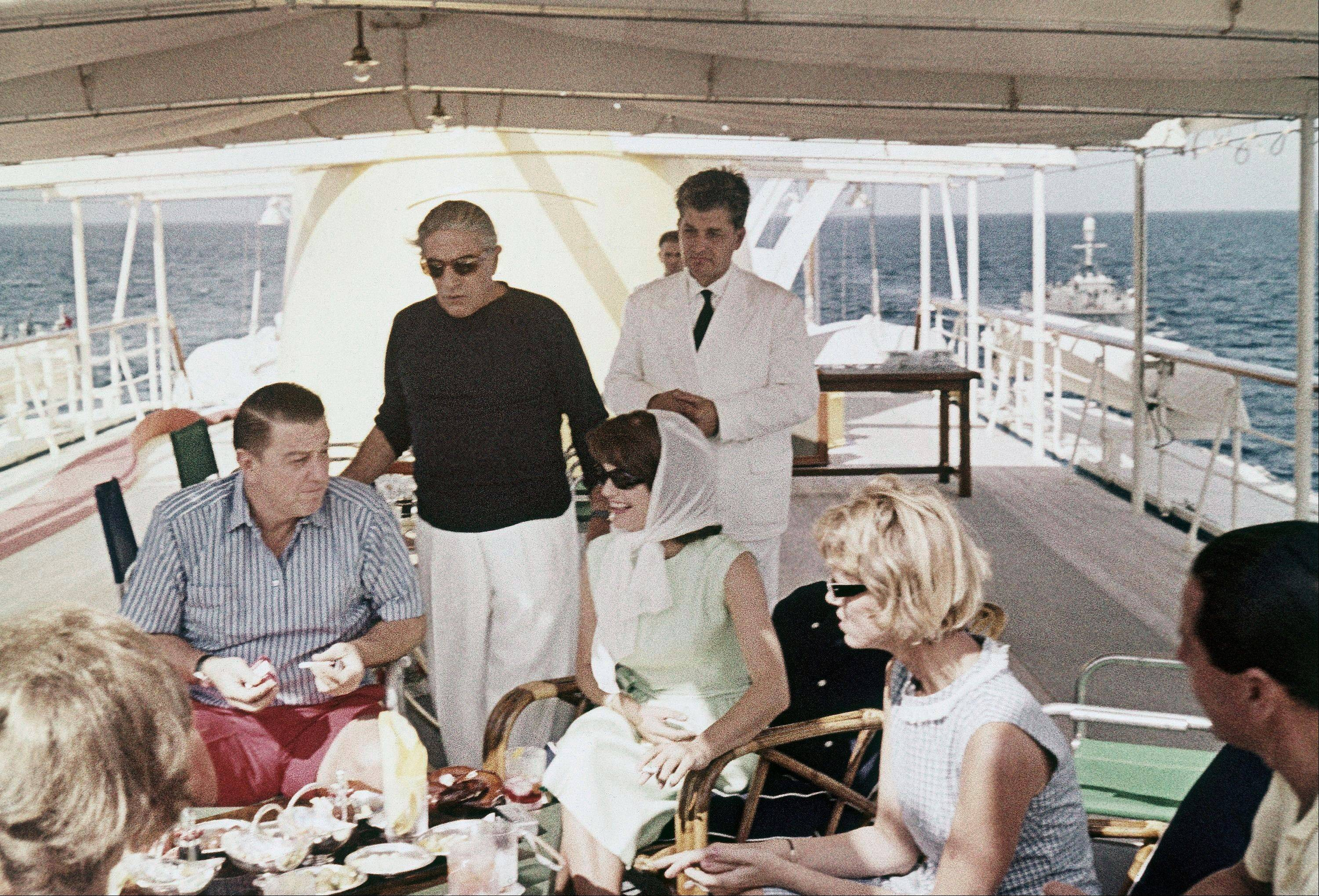 This is a 1963 file photo of Aristotle Onassis, standing with black shirt, as he joins, Jaqueline Kennedy and Franklin Roosevelt Jr., on board the Onassis yacht Christina in the Mediterranean.