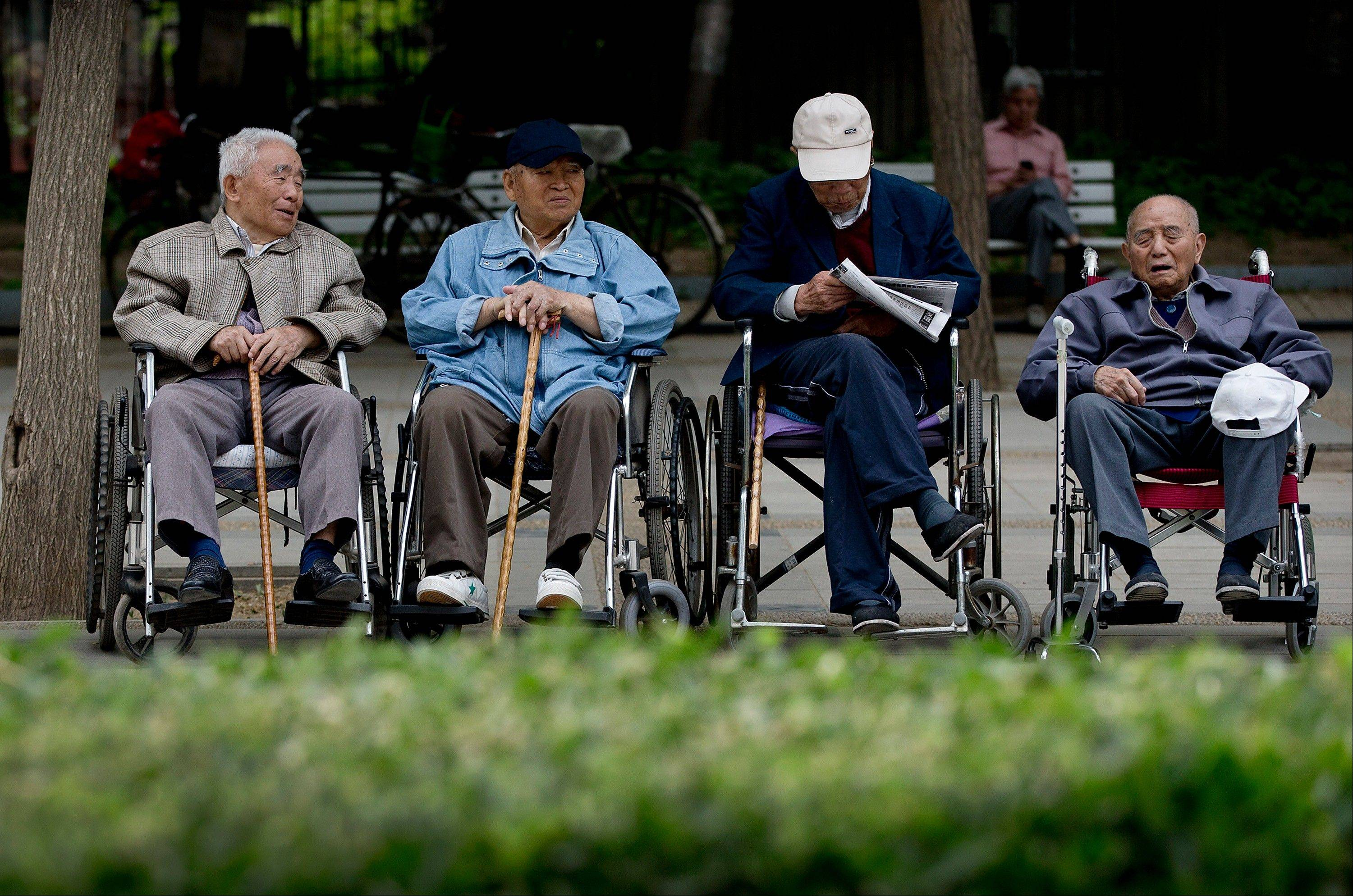 A group of elderly men take a rest on their wheelchairs at a park in Beijing. New wording in the law requiring people to visit or keep in touch with their elderly parents or risk being sued has come into force as China faces increasing difficulty in caring for its aging population.