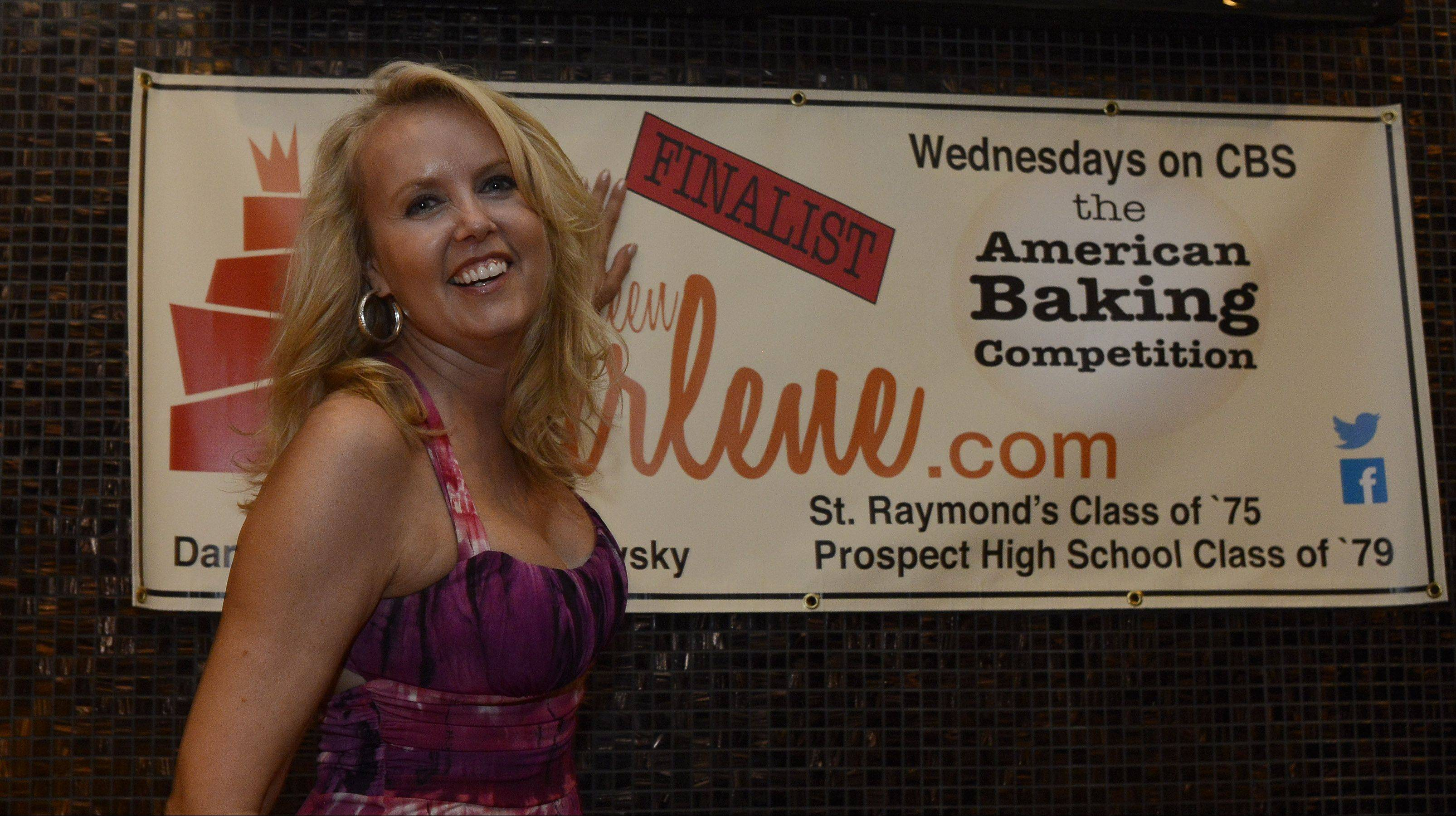 "Darlene Pawlukowsky, a contestant on CBS' ""The American Baking Competition,"" applies a sticker to a banner that reads ""finalist"" after watching the show Wednesday with friends and family at Emerson's Ale House in Mount Prospect. Pawlukowsky will be marching in the Fourth of July parade today in Mount Prospect."
