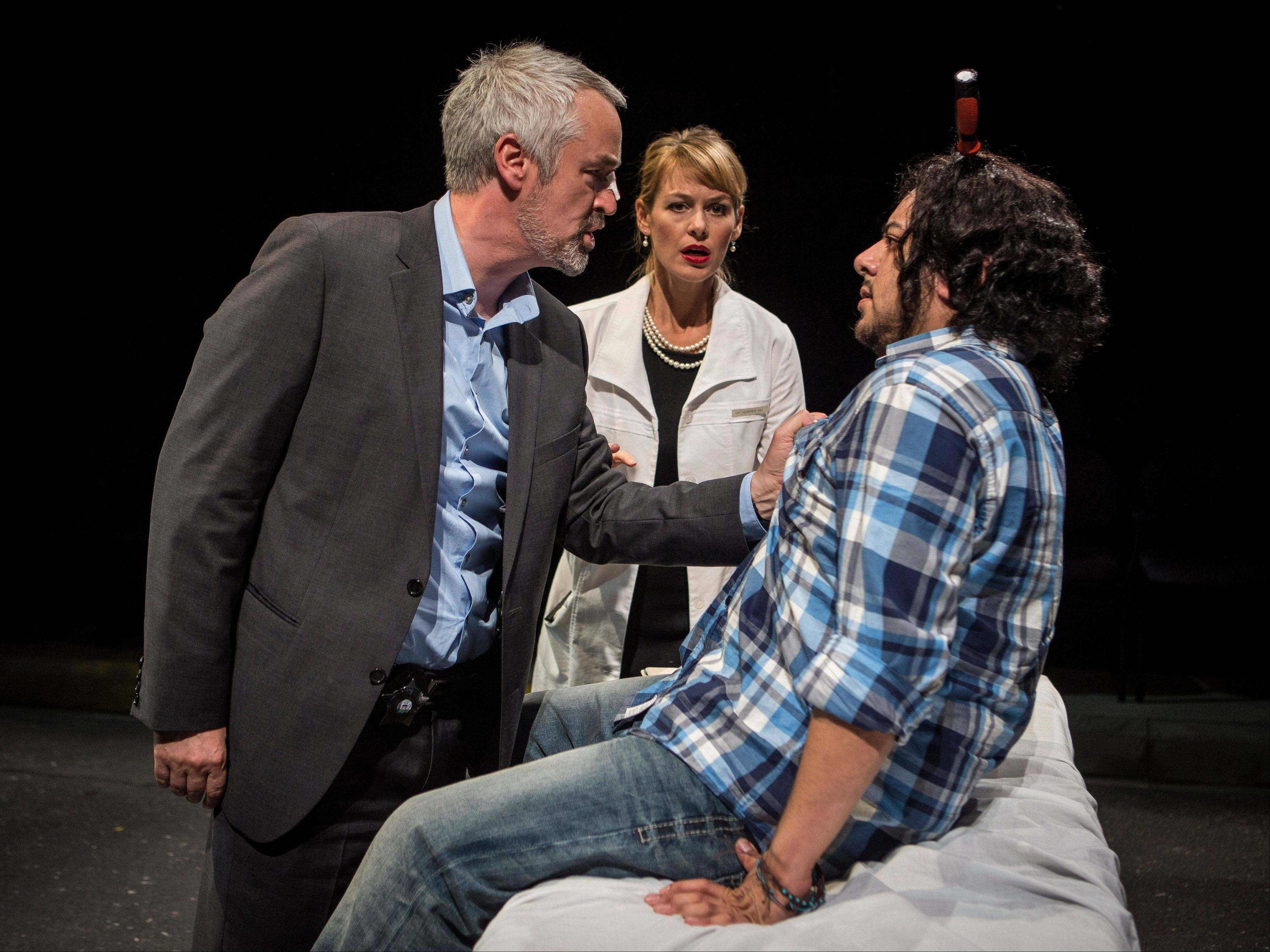 "Over the objection of psychiatrist Susan Howren (Beth Lacke), center, Detective Podaris (Philip R. Smith), left, interrogates the hapless Stewart (Eddie Martinez), right, whose dispute with his brother left him with a screwdriver in his skull in Keith Huff's latest dark comedy, ""Big Lake Big City,"" running at Lookingglass Theatre."