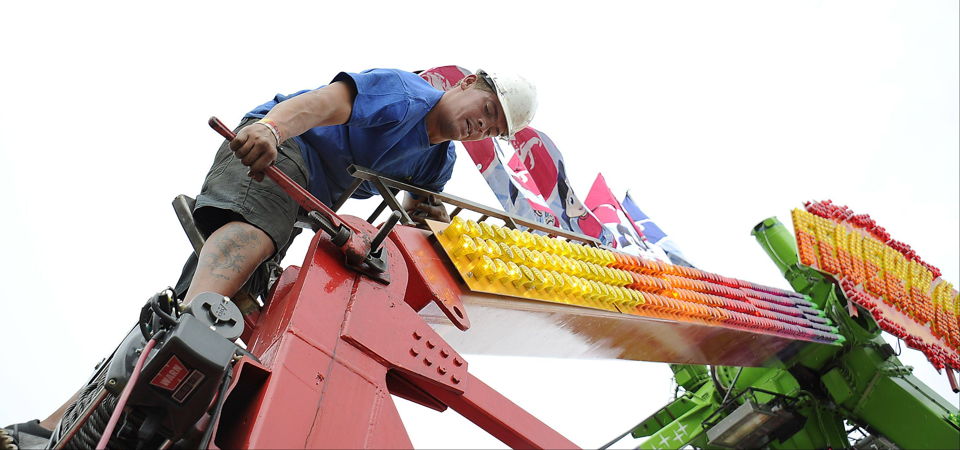 Jaundre Thompson of Johannesburg, South Africa wrenches a nut and bolt into place at the Frontier Days carnival.