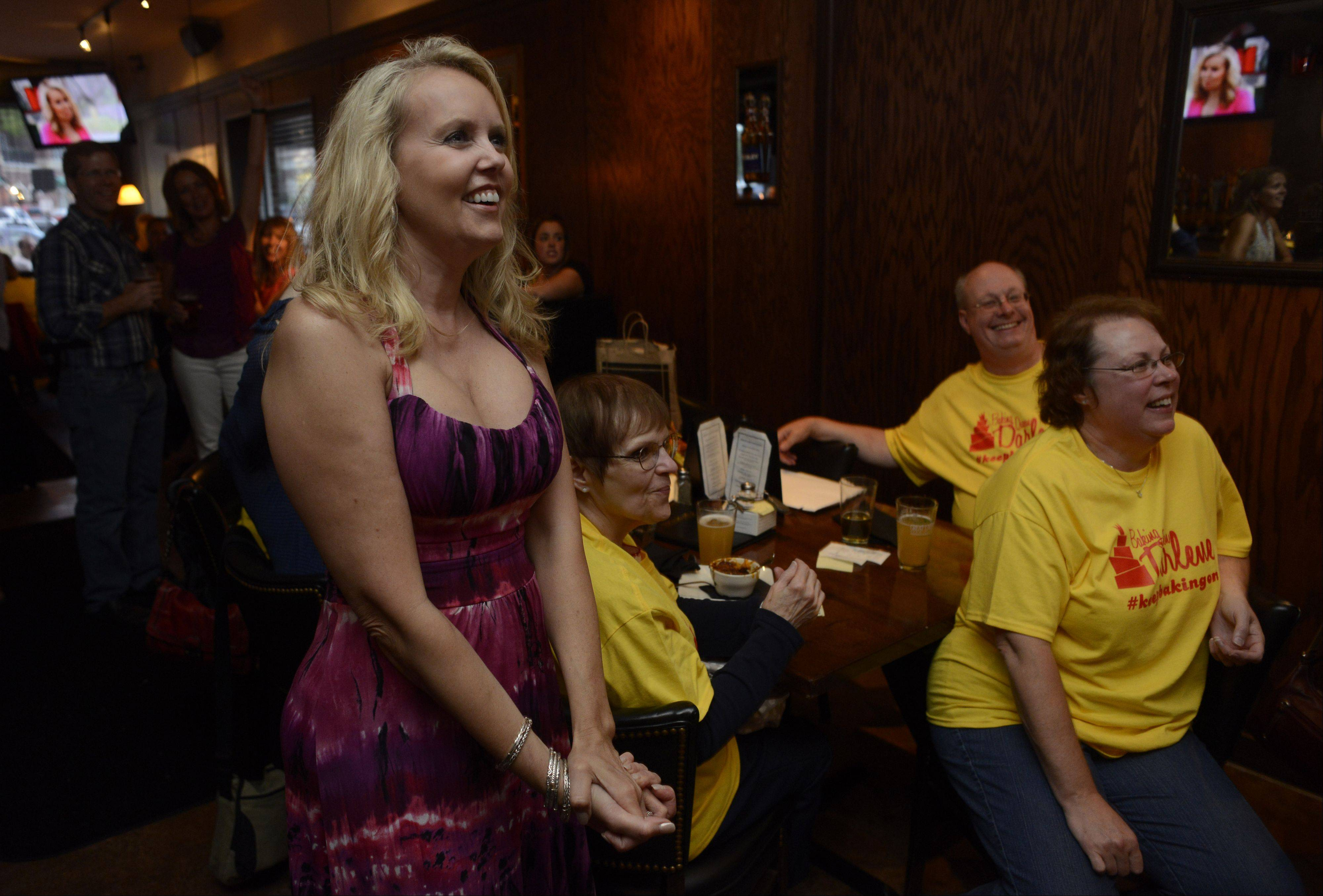 "Darlene Pawlukowsky, a contestant on CBS' ""The American Baking Competition,"" watches the show with Wednesday night friends and family at Emerson's Ale House in Mount Prospect. Pawlukowsky will march today in the Fourth of July parade in Mount Prospect."