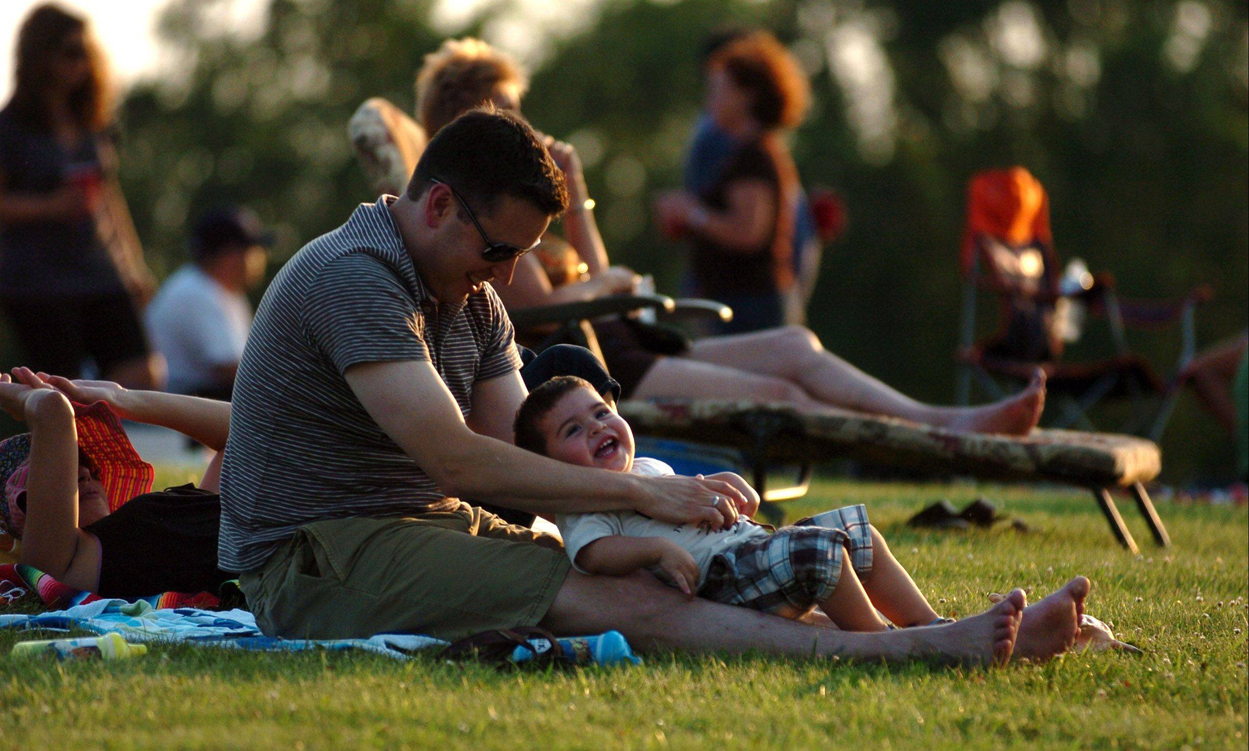 James Cook of Cary plays with his 16-month-old son Felix at a previous Cary Kickoff to Fourth of July at Lions Park. This year's event, set for Wednesday, July 3, features live music, food, and fireworks.