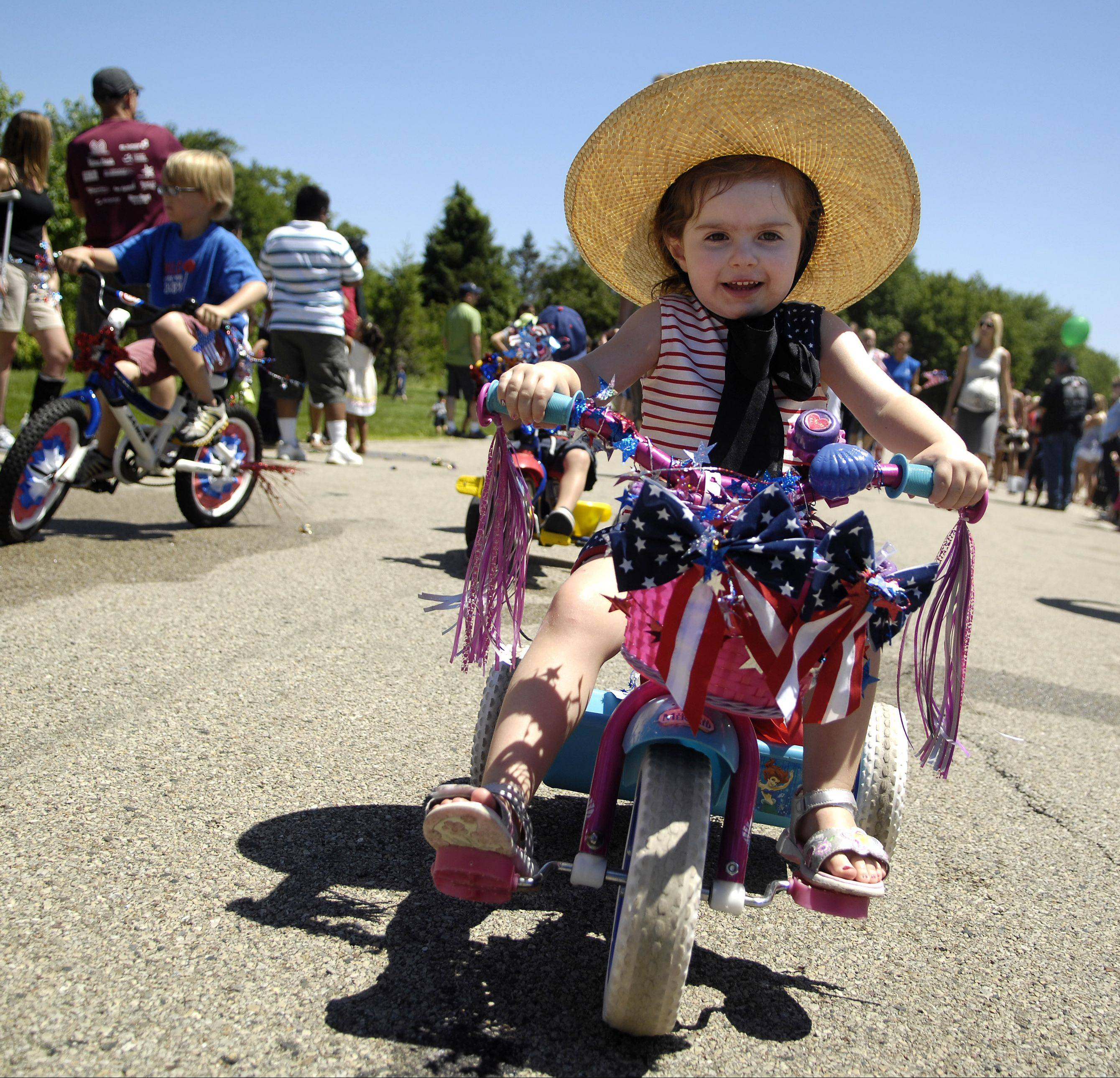 Chloe Coffey, 3, of Lake in the Hills rides her decorated trike during Sleepy Hollow's Fourth of July parade. The village will hold an all-day celebration on the Fourth of July, starting with a fun run and finishing with fireworks.