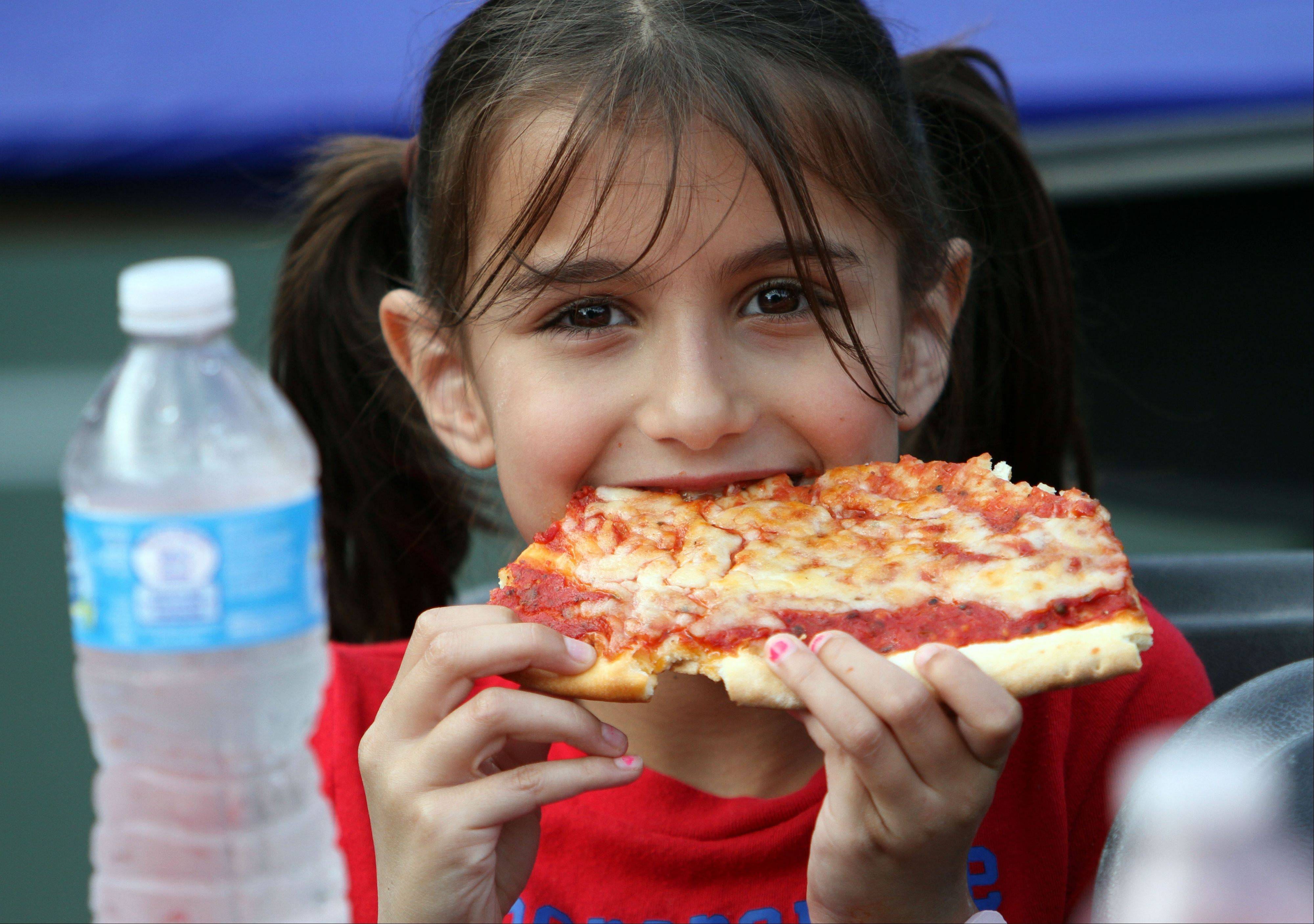 Eight-year-old Amanda Bloom of Lincolnshire eats pizza during Lincolnshire's Red, White & Boom celebration Wednesday in Spring Lake Park.