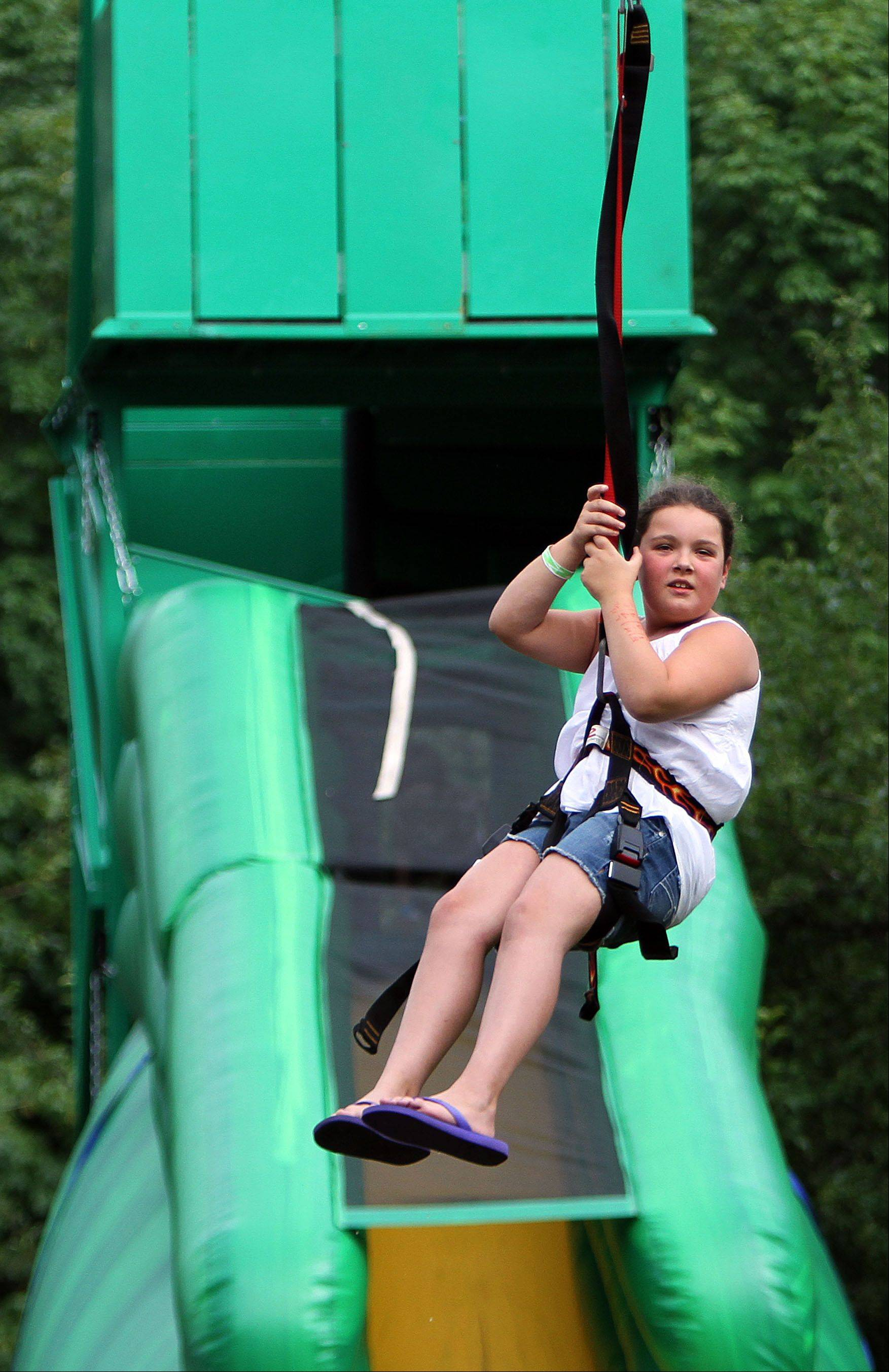Eight-year-old Kaitlin Driscoll of Lincolnshire tries out a zip line during Lincolnshire's Red, White & Boom celebration Wednesday in Spring Lake Park.