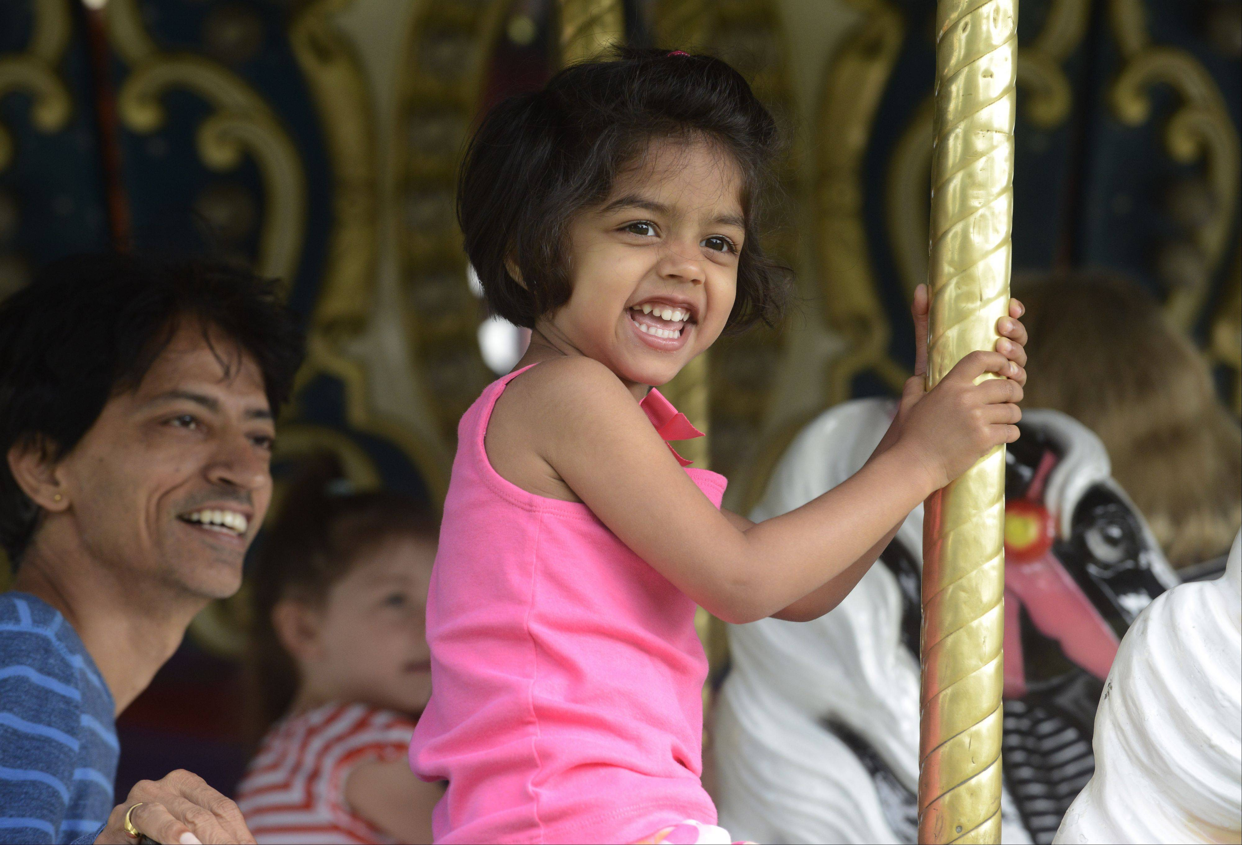 Dhira Ayyagari, 3, of Arlington Heights rides the carousel with her dad, Narsu, during Frontier Days in Arlington Heights Wednesday.