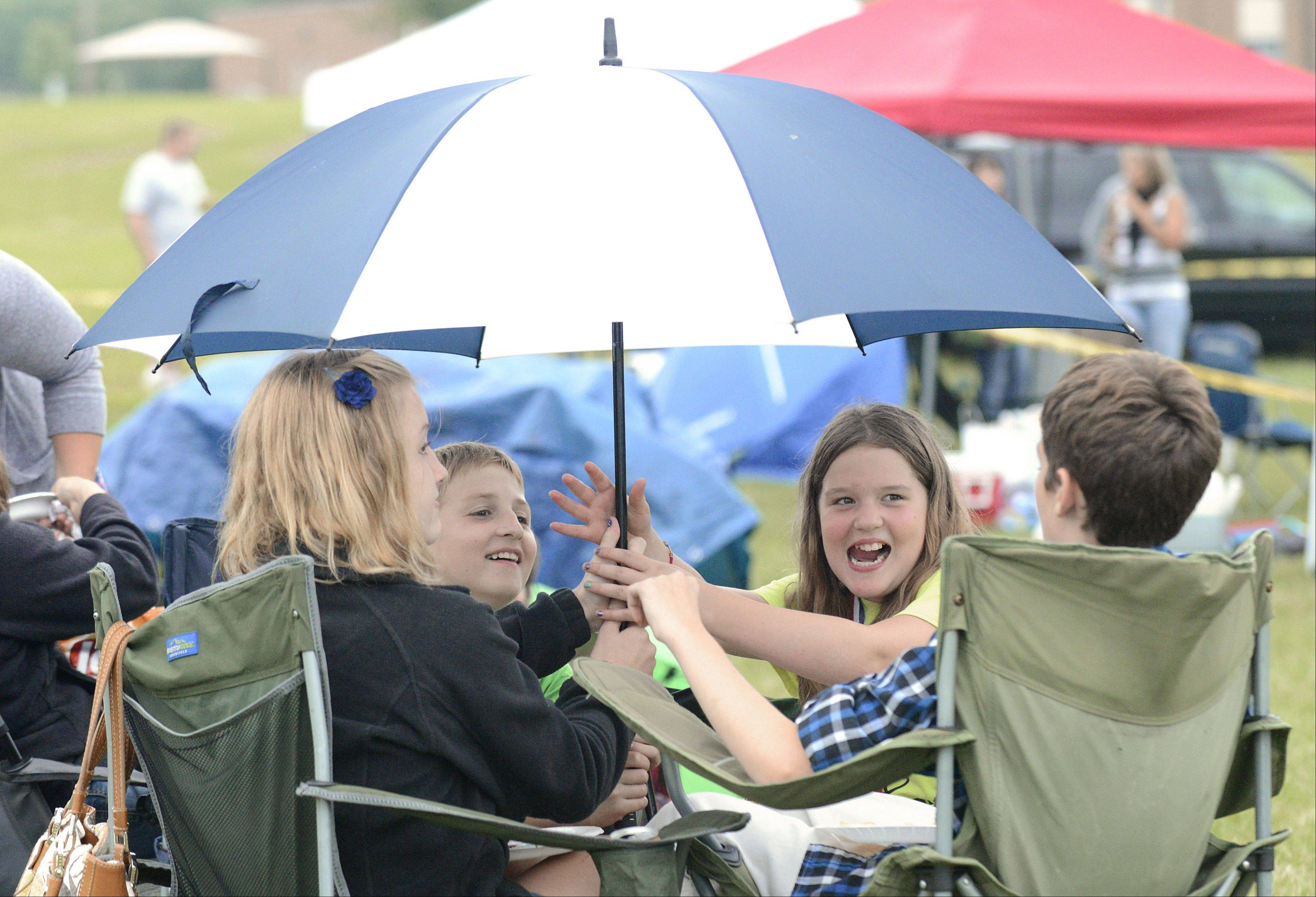 Gracie Strader, 10, of Geneva laughs as their umbrella bops her big brother, Colin, 13, on the head. Gracie, Colin, and friends Hannah Schwichtenberg, 13, and her brother Connor, 10, all of Genoa, huddled under the umbrella prior to the planned fireworks at Burlington Township Park.