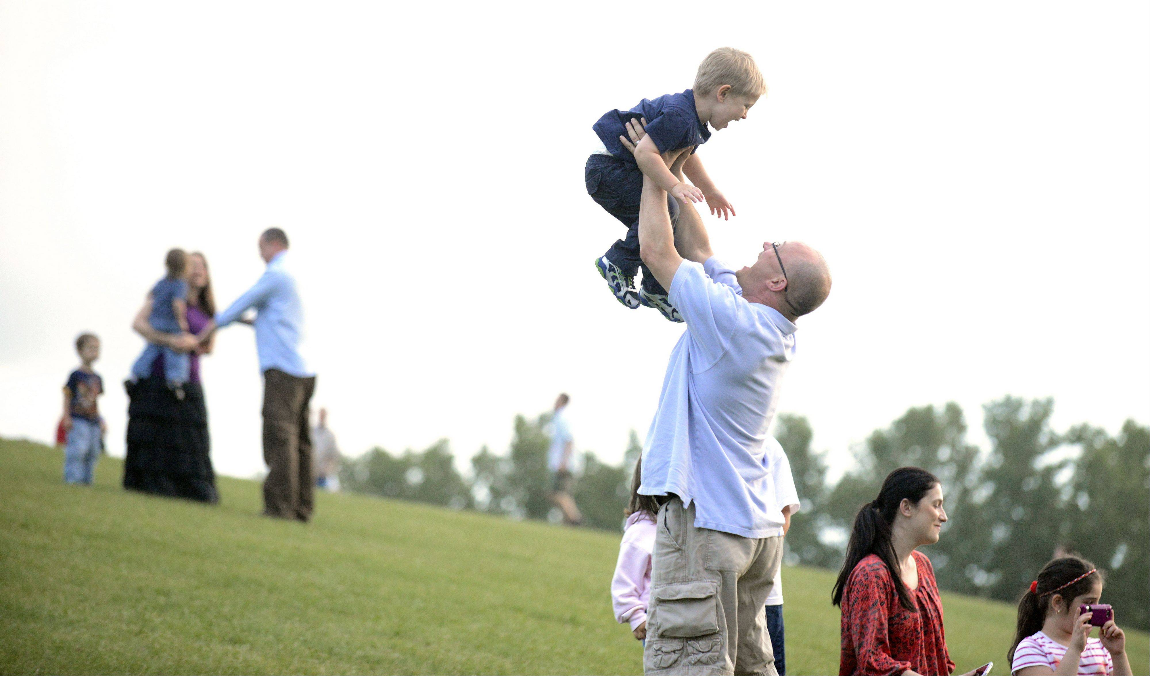 Dan Murphy of Cary lifts his son, Ian, 2, into the air while they listen and dance to the music by rock cover band, Spoken Four, at Cary's Summer Celebration.