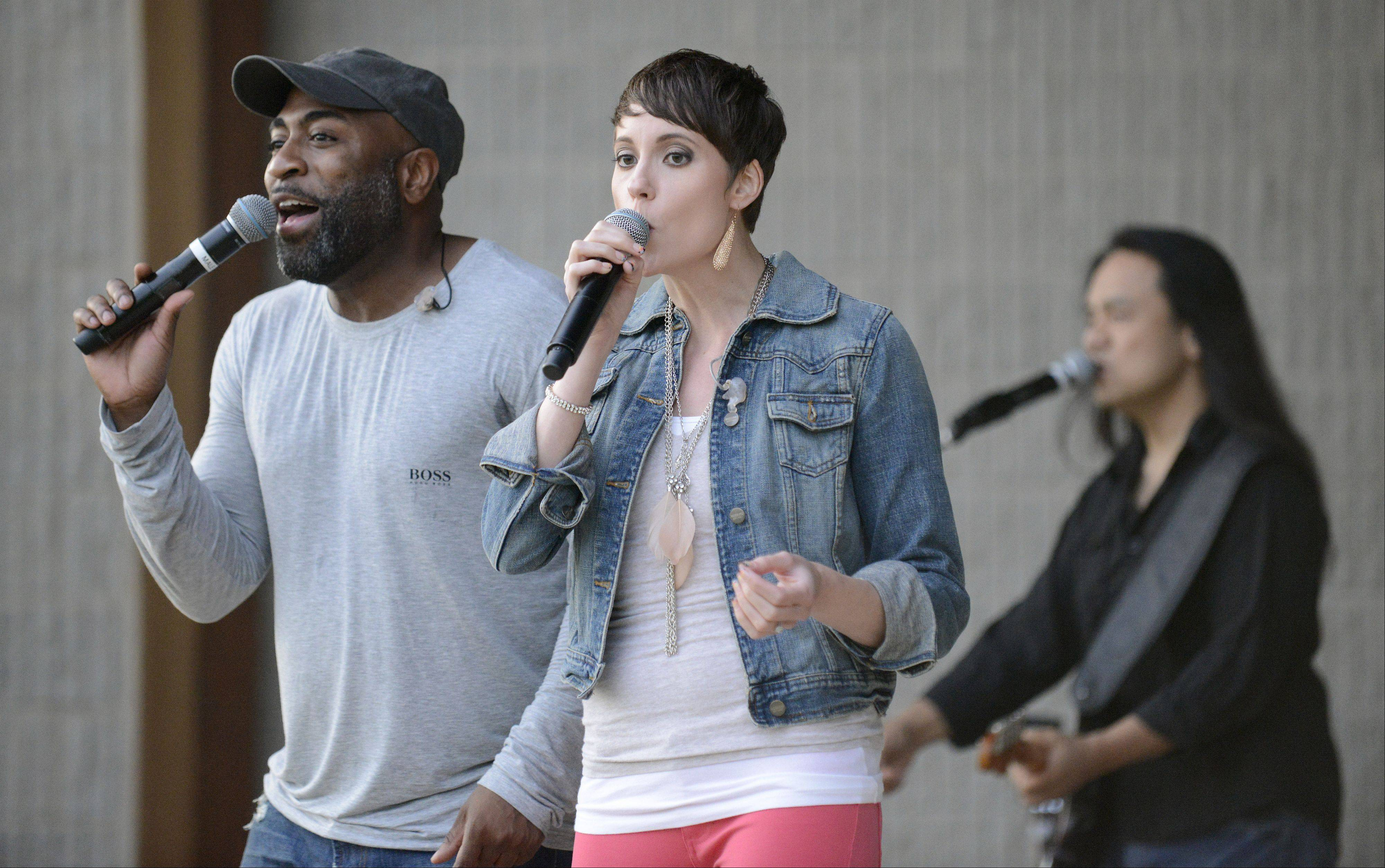 Shannon Stevenson, left, Becky Schneider, center, and Domingo Castillo, right, perform with rock cover band Spoken Four at Cary's Summer Celebration in Lions Park.