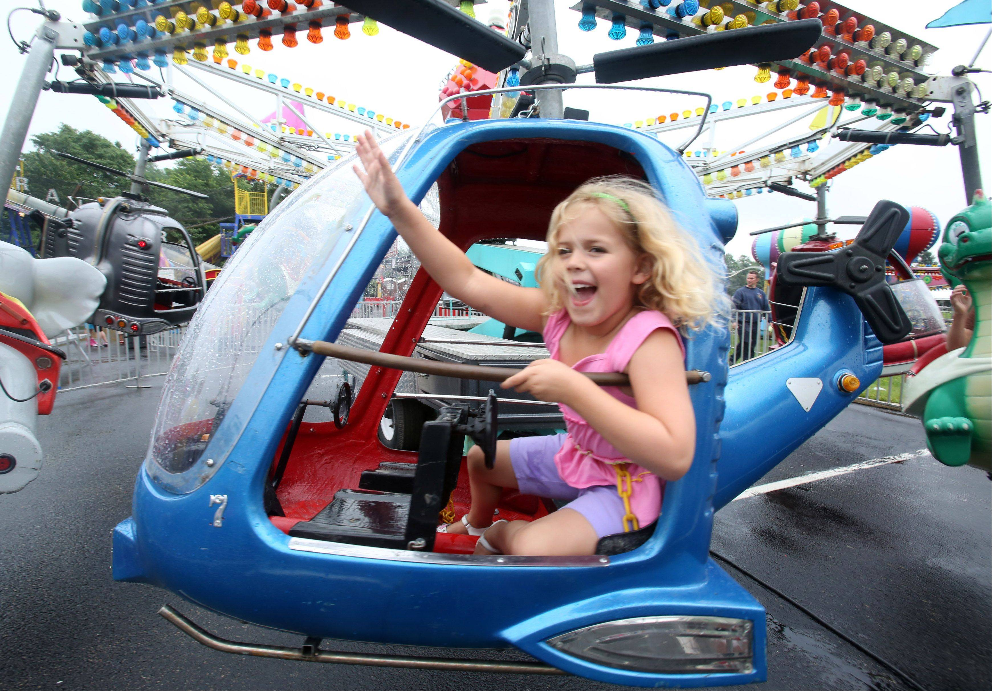 Savah Blume, 6, of Palatine waves to her brother, Kevin, 9, and her mother, Julie, as she rides the helicopter Wednesday, the opening day of Palatine Jaycees' 56th annual Hometown Fest.