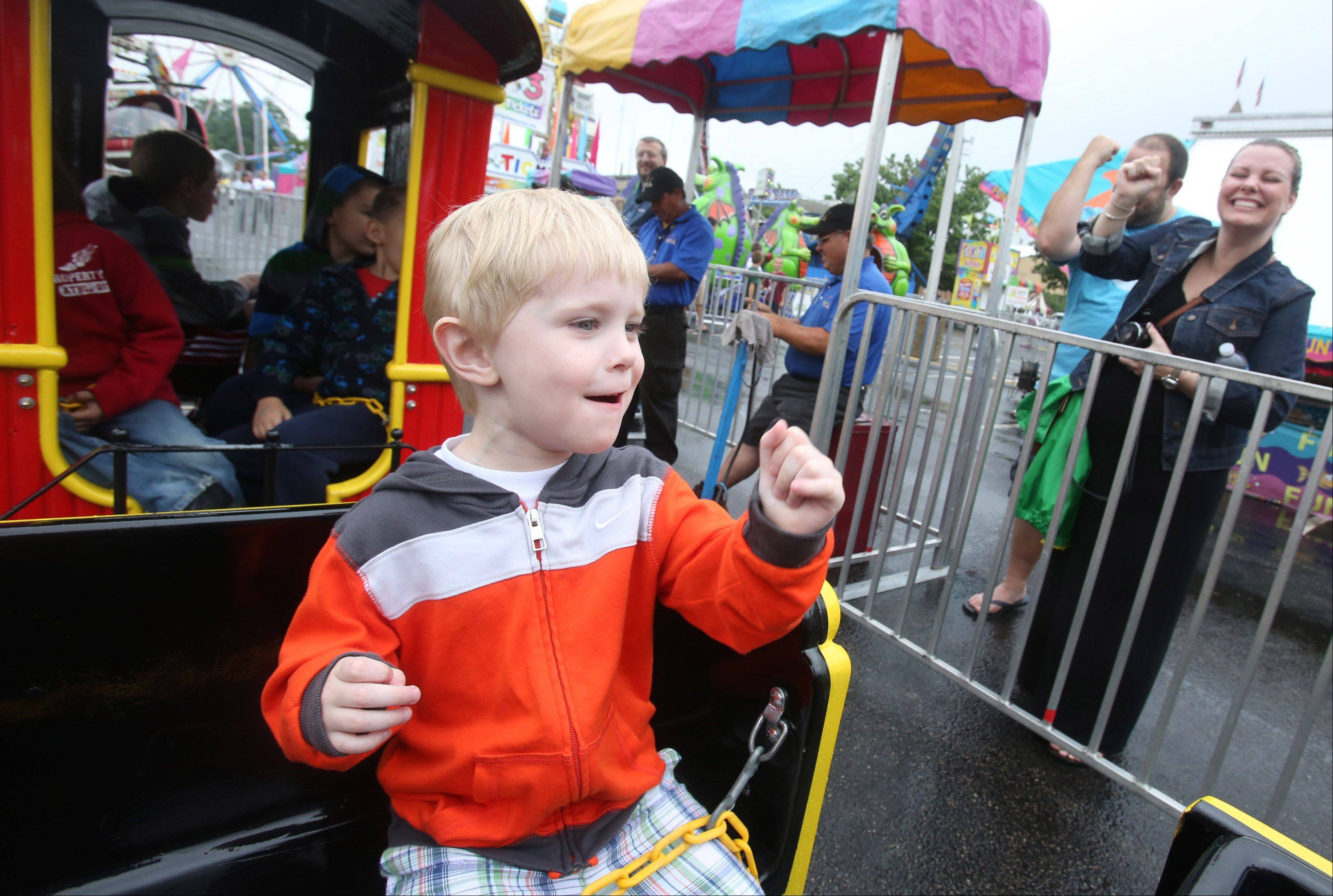 Jack Gargano, 3, of Rolling Meadows makes a choo-choo train horn sign to his parents Scott and Megan, right, during the first day of Palatine Jaycees' 56th annual Hometown Fest at Community Park.