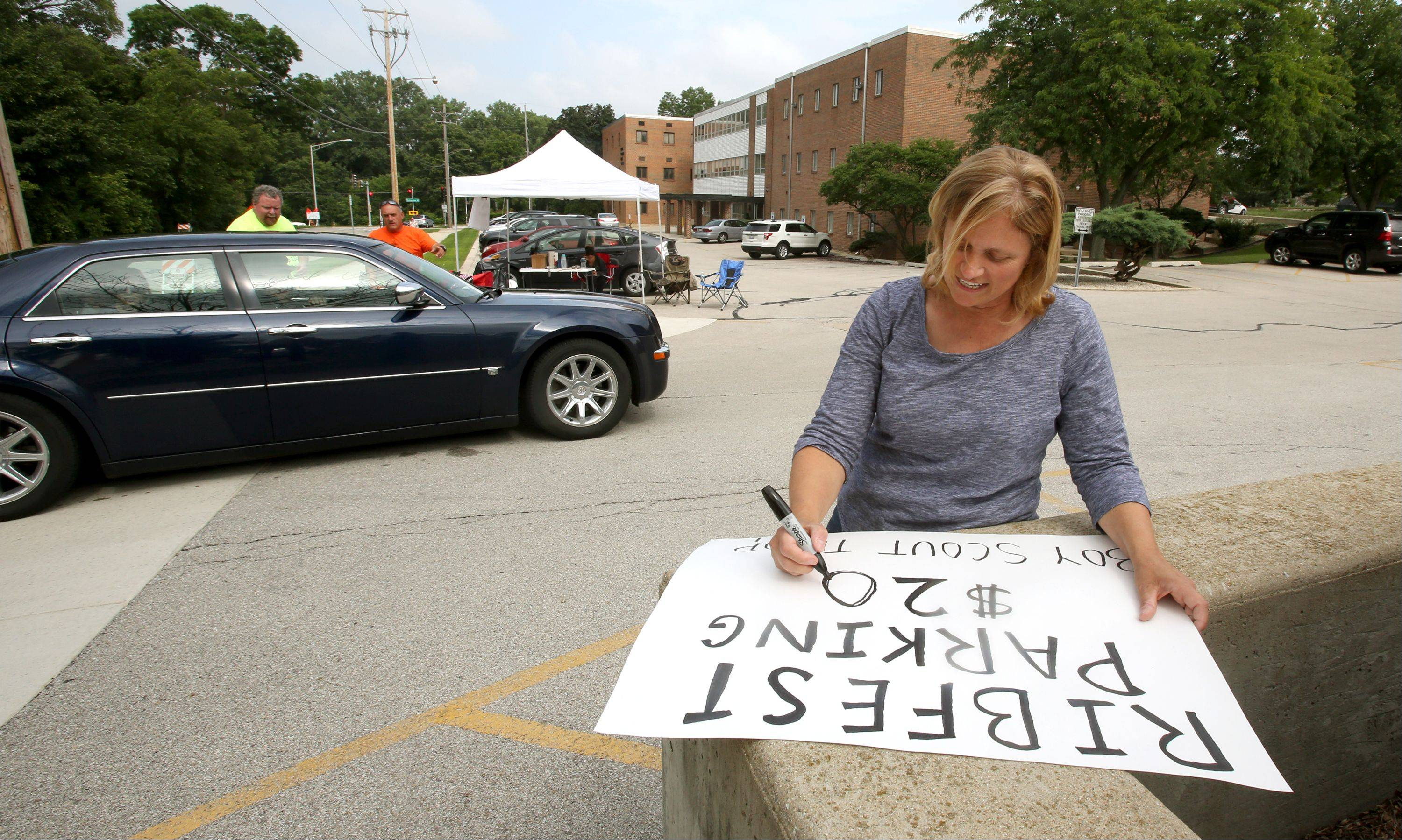 Susan Sullivan finishes a parking sign Wednesday afternoon for Boy Scout Troop 111, which had 170 Ribfest parking spots along Martin Avenue to sell for $20 each as the 26th annual event kicked off in Knoch Park.