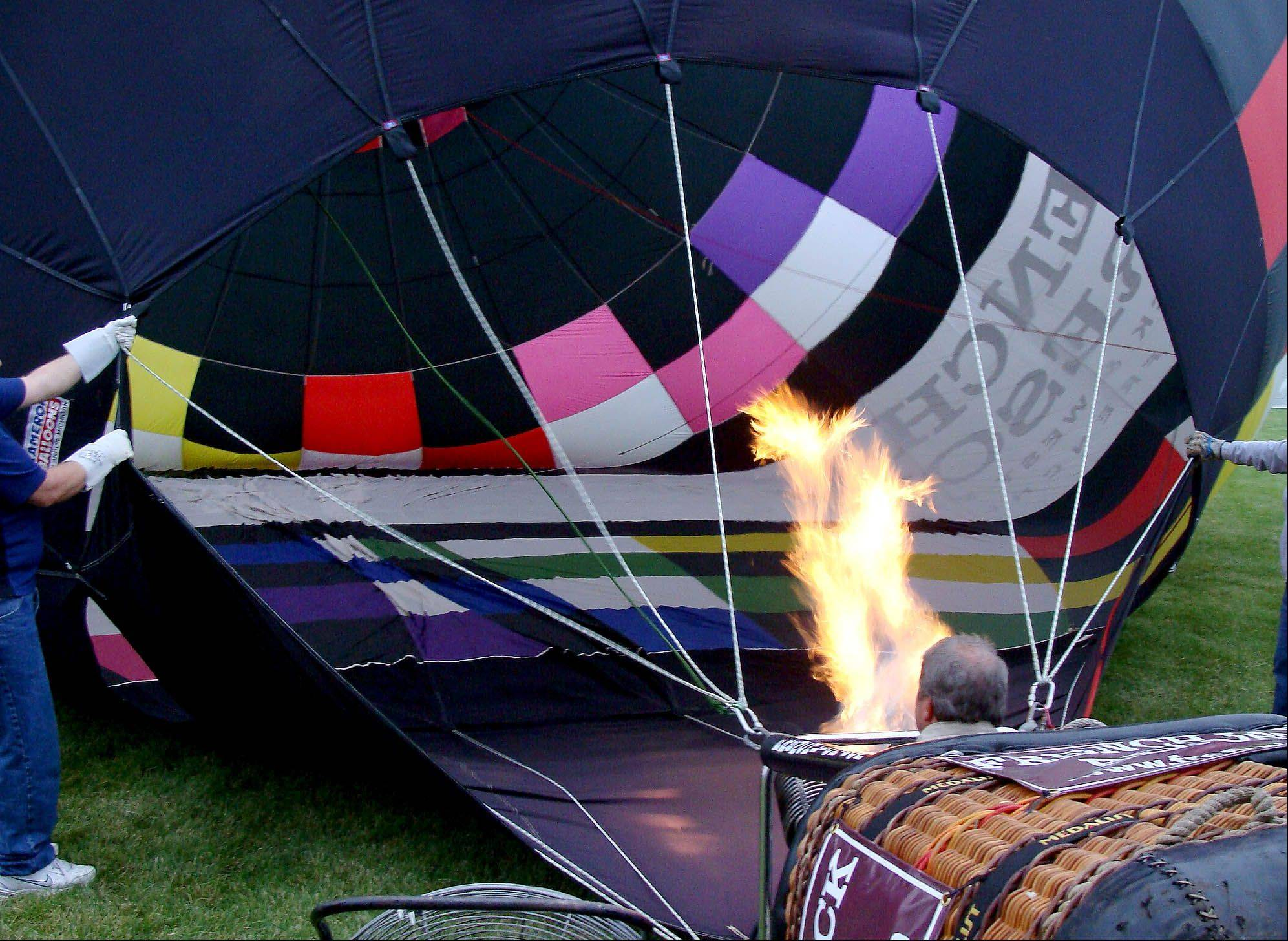 Jerry Copas inflates his balloon from inside the basket Wednesday. His balloon, advertising French Lick Resort in Indiana, is one of more than 20 featured at the festival.