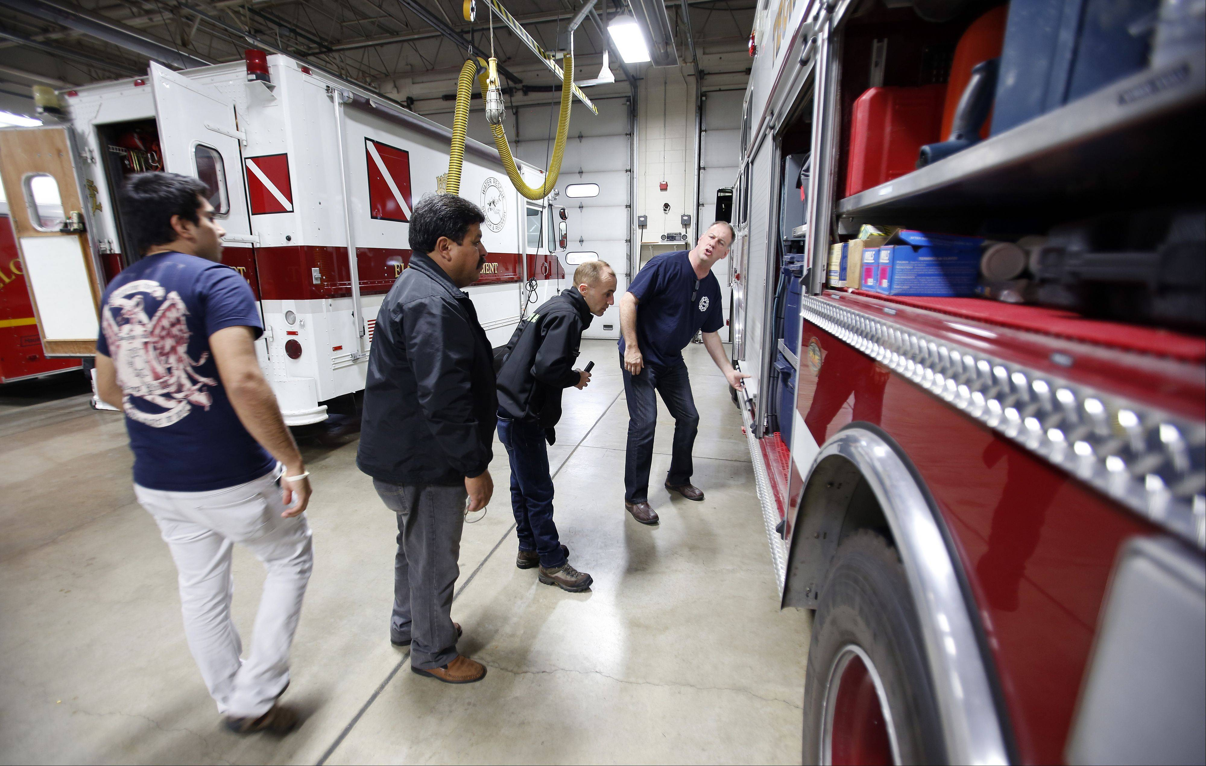 Elgin Fire Department Lt. Bob Bedard, far right, explains the inner workings of a fire truck to the Chile delegation Wednesday at the Big Timber Road station. A delegation of six people from Chile arrived in Elgin on Tuesday and will stay through Monday.
