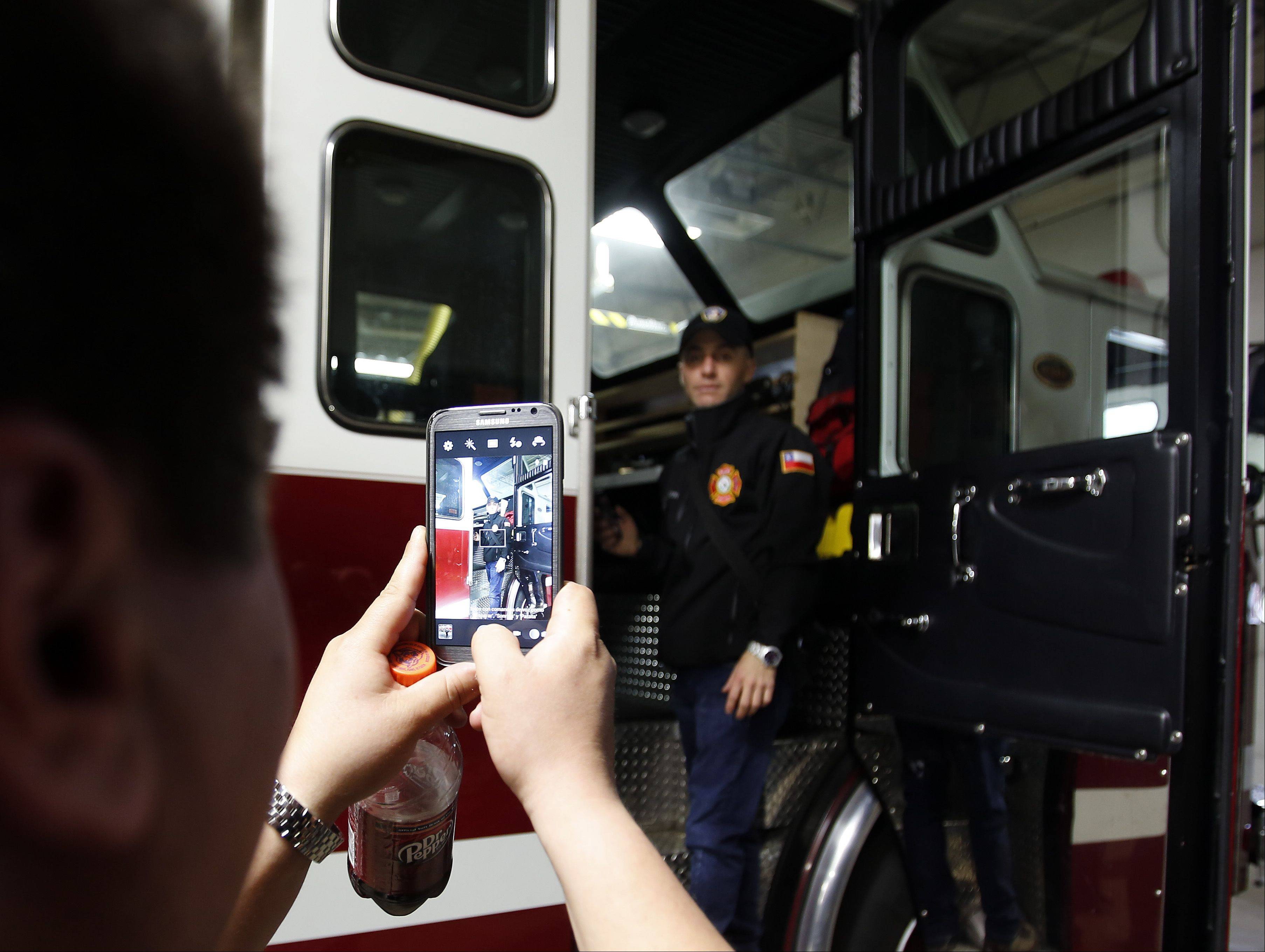J.M. Lavin B. poses for a picture on one of the Elgin Fire Department trucks during a tour of the Big Timber Road station Wednesday. Lavin is the Inspector General for Chile's Urban Search and Rescue squad.