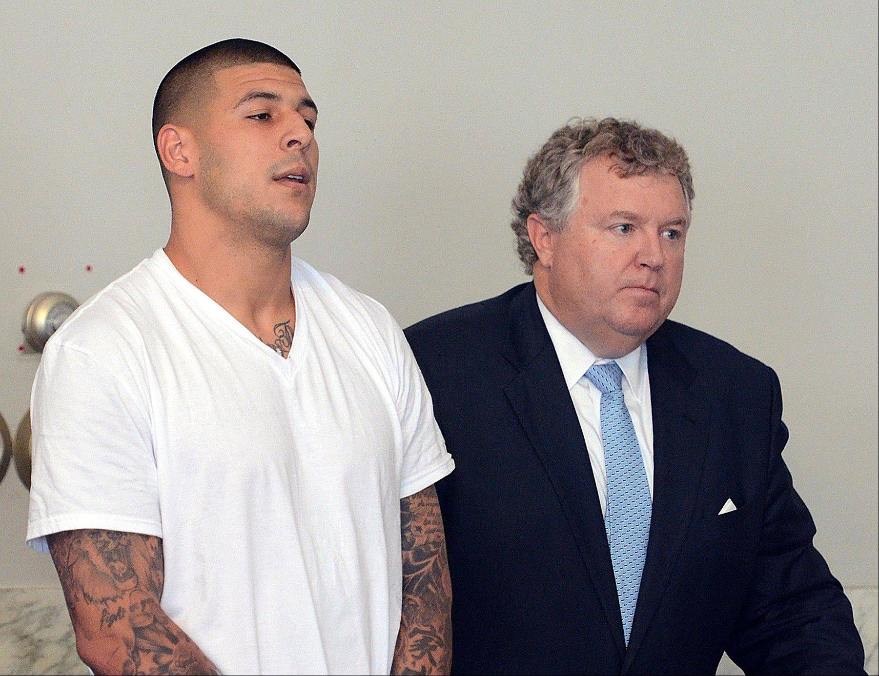 Aaron Hernandez, left, stands with his attorney, Michael Fee, right, during arraignment. Since Hernandez was arrested last week in the shooting death of a friend whose body was found a mile away from his home, a portrait has emerged of a man whose life away from the field included frequent connections with police-related incidents that started as long ago as his freshman year at the University of Florida.