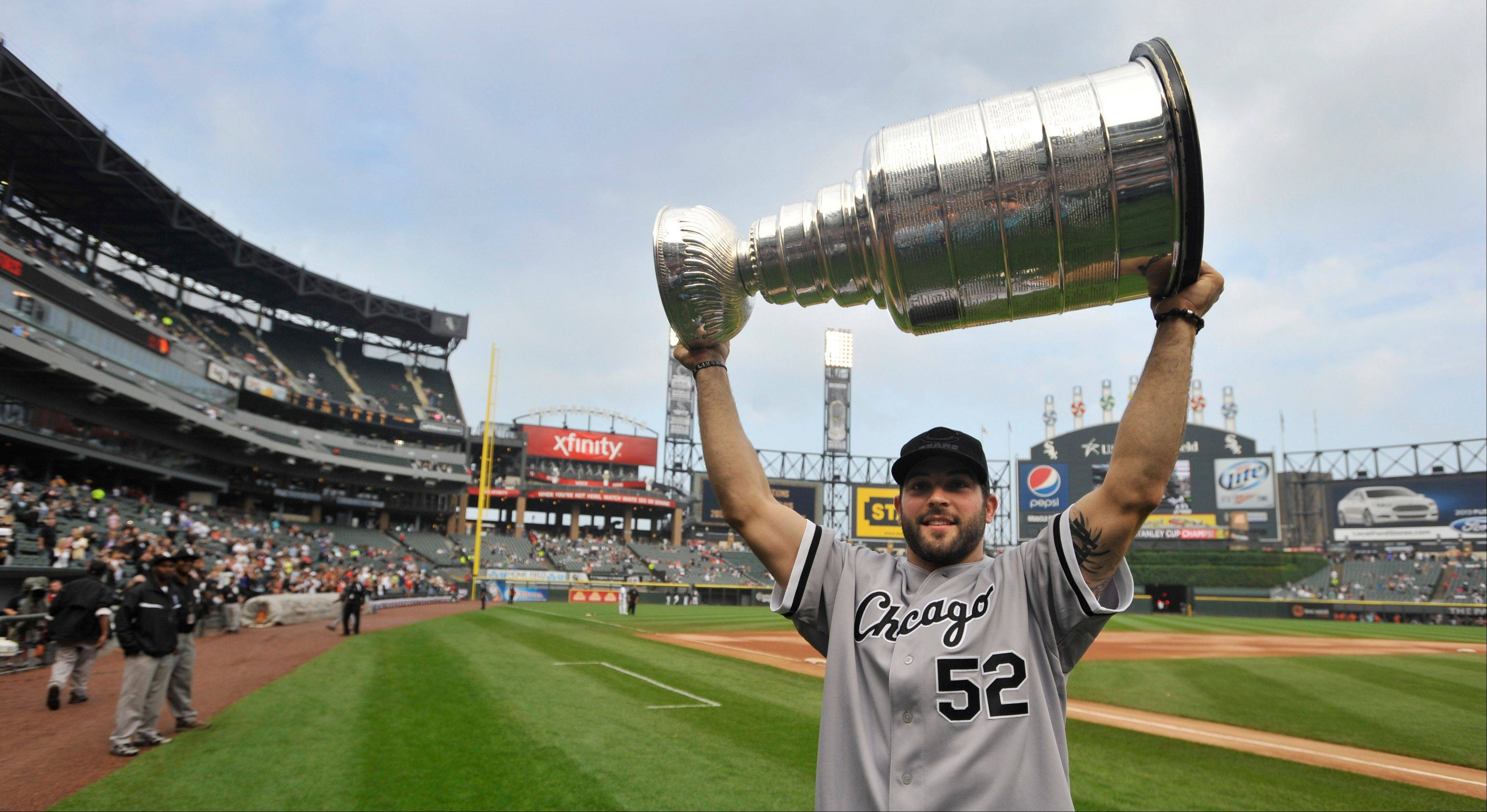 Blackhawks player Brandon Bollig carries the Stanley Cup after throwing out a ceremonial first pitch before the White Sox-Orioles game at U.S. Cellular Field in Chicago.