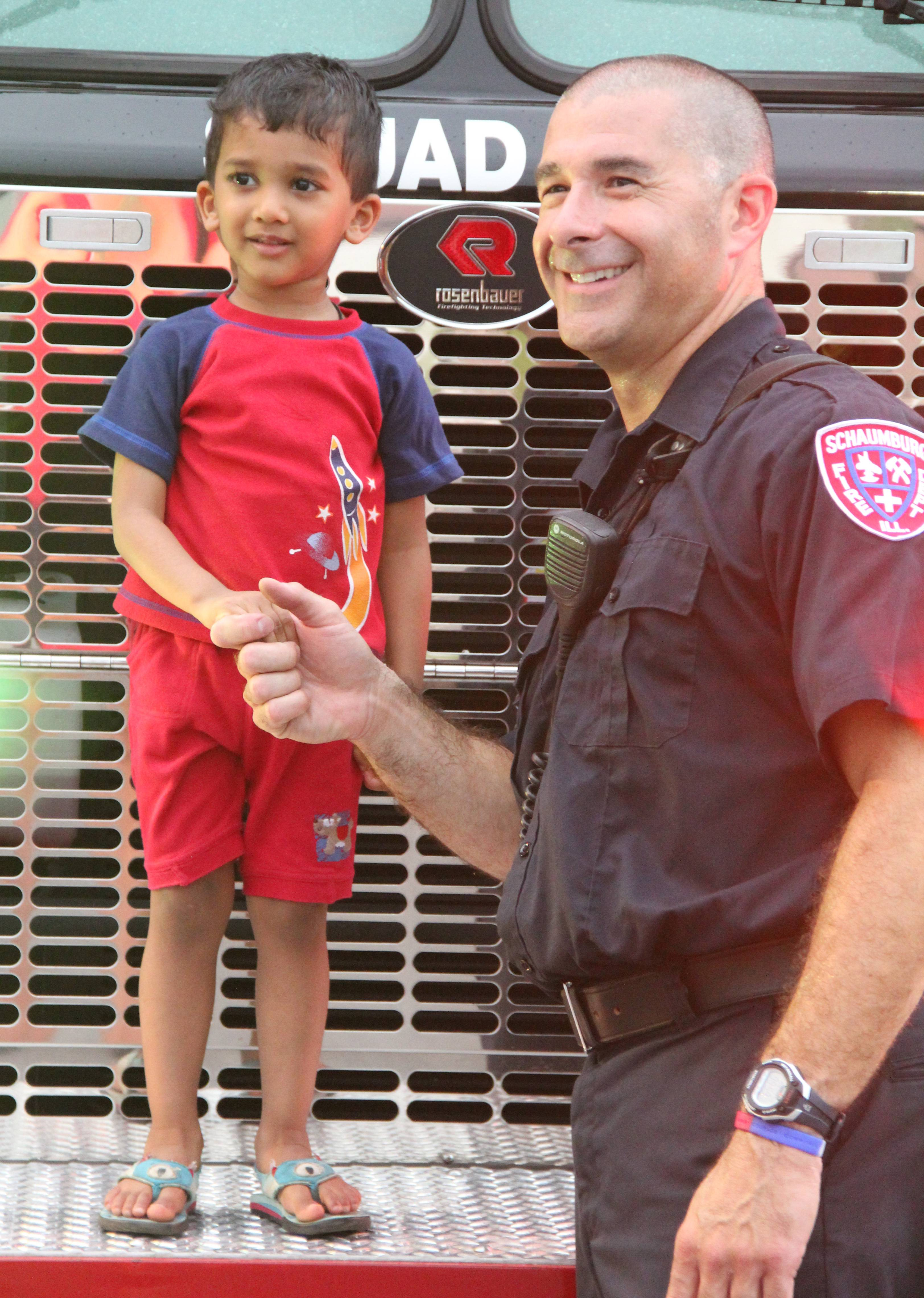 A firefighter with a National Night Out participant at a past event.