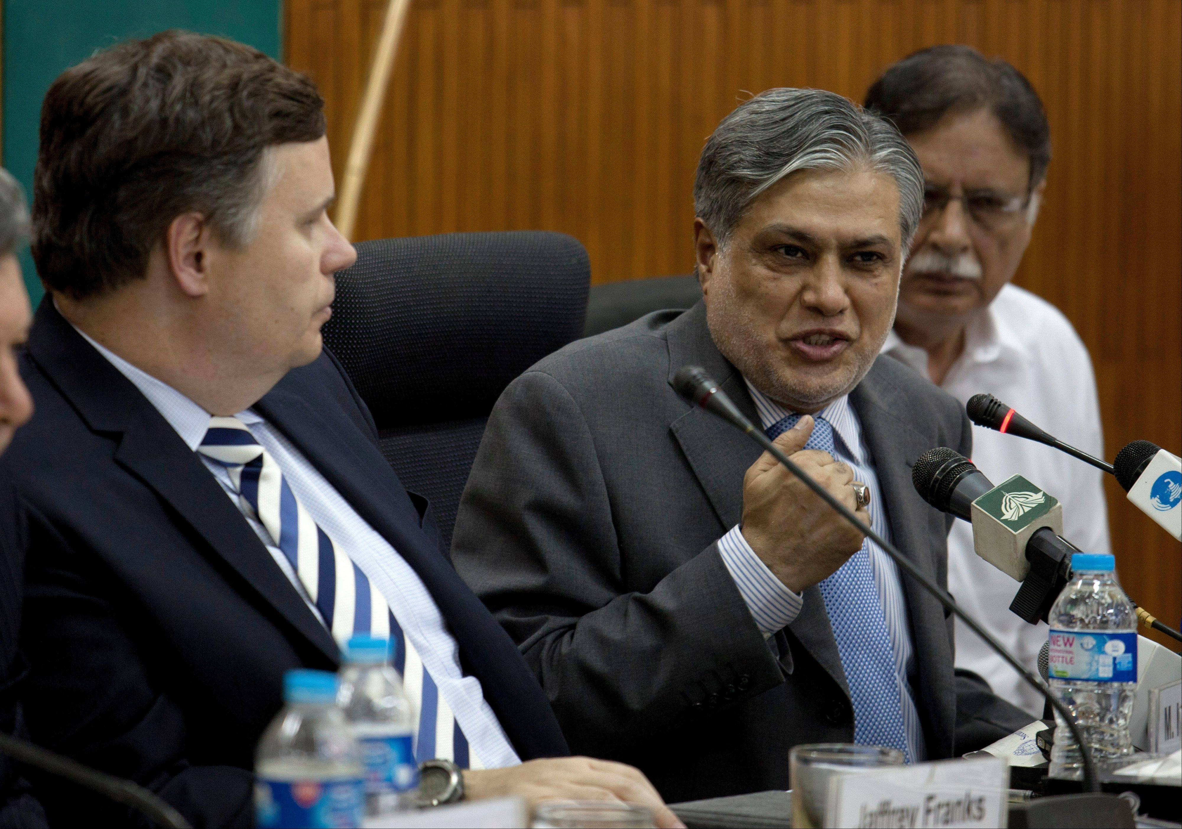 Pakistani Finance Minister Muhammad Ishaq Dar, center addresses a news conference with IMF mission chief Jeffrey Franks, left, at the finance ministry in Islamabad, Pakistan on Thursday. Pakistan and the International Monetary Fund have reached an initial agreement on a bailout of at least $5.3 billion to stave off an economic crisis as the countryís foreign reserves dip perilously low, officials said Thursday.
