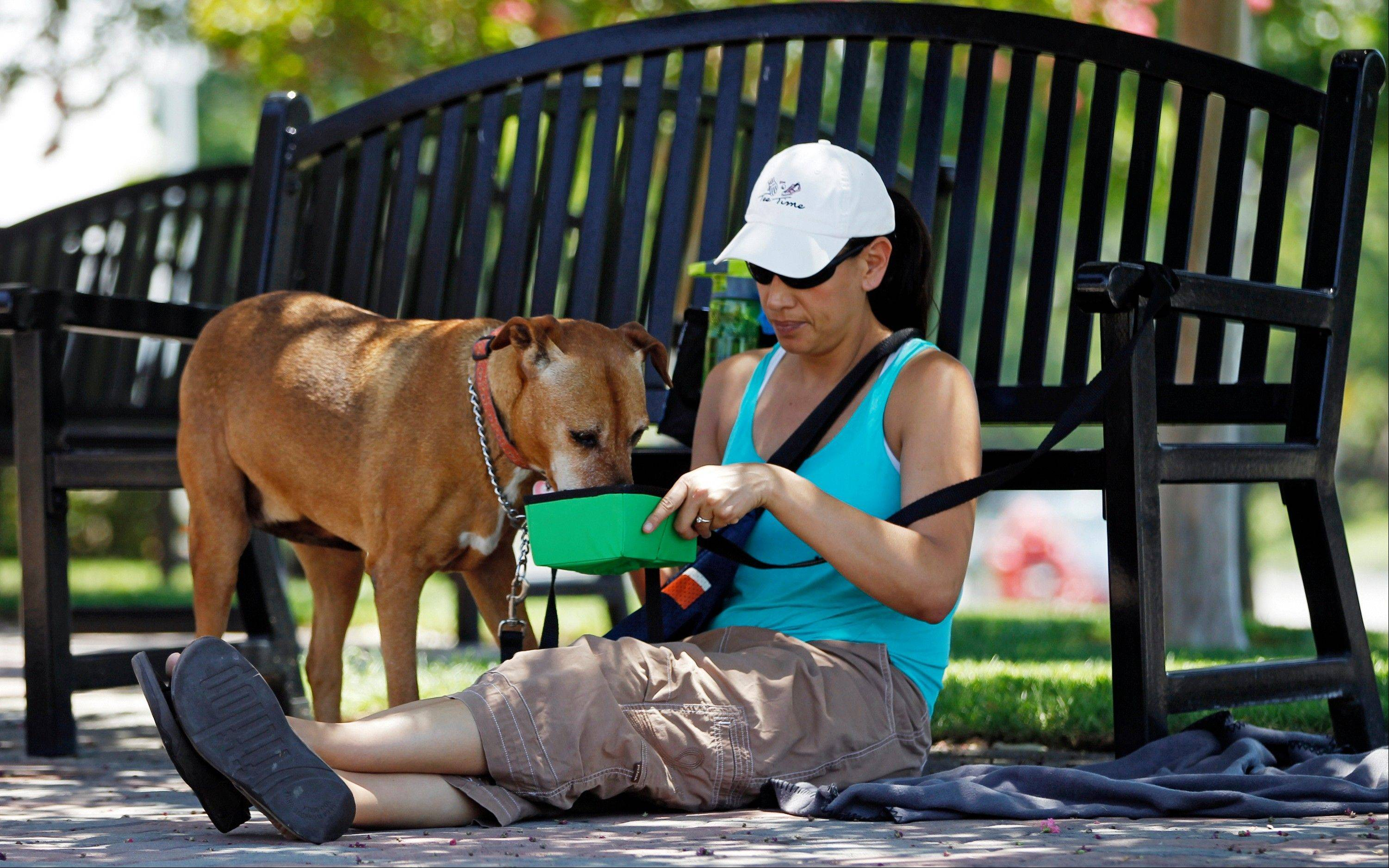 Monee Hauducoeur, from Upland, Calif., keeps a bowl of fresh water for her dog, Summer, as she awaits in the shade to adopt another dog outside the City of Rancho Cucamonga Animal Care & Adoption Center in Rancho Cucamonga, Calif.