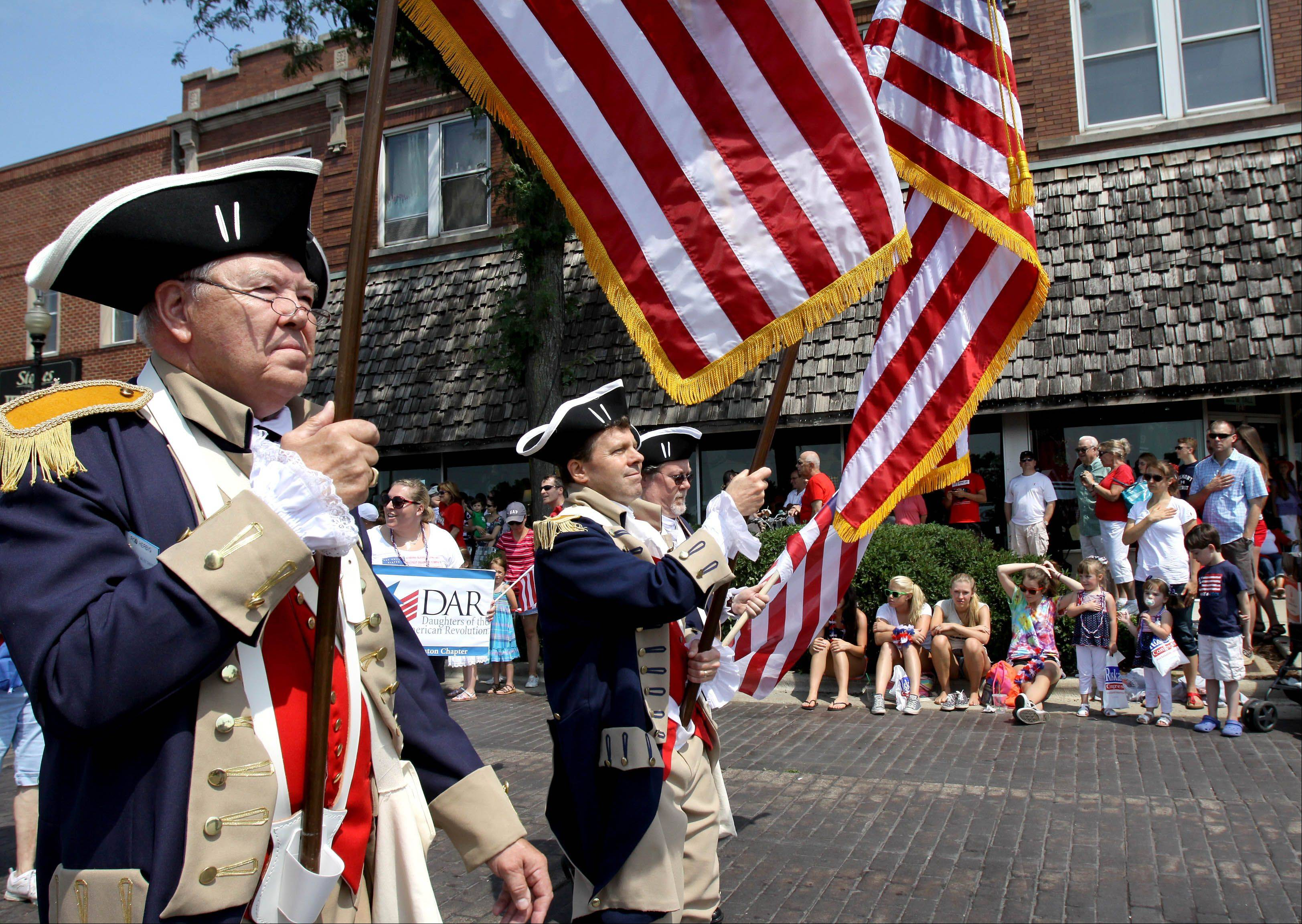 Members of the Sons of the American Revolution Illinois, march down Front Street in the 4th of July parade in Wheaton on Thursday.