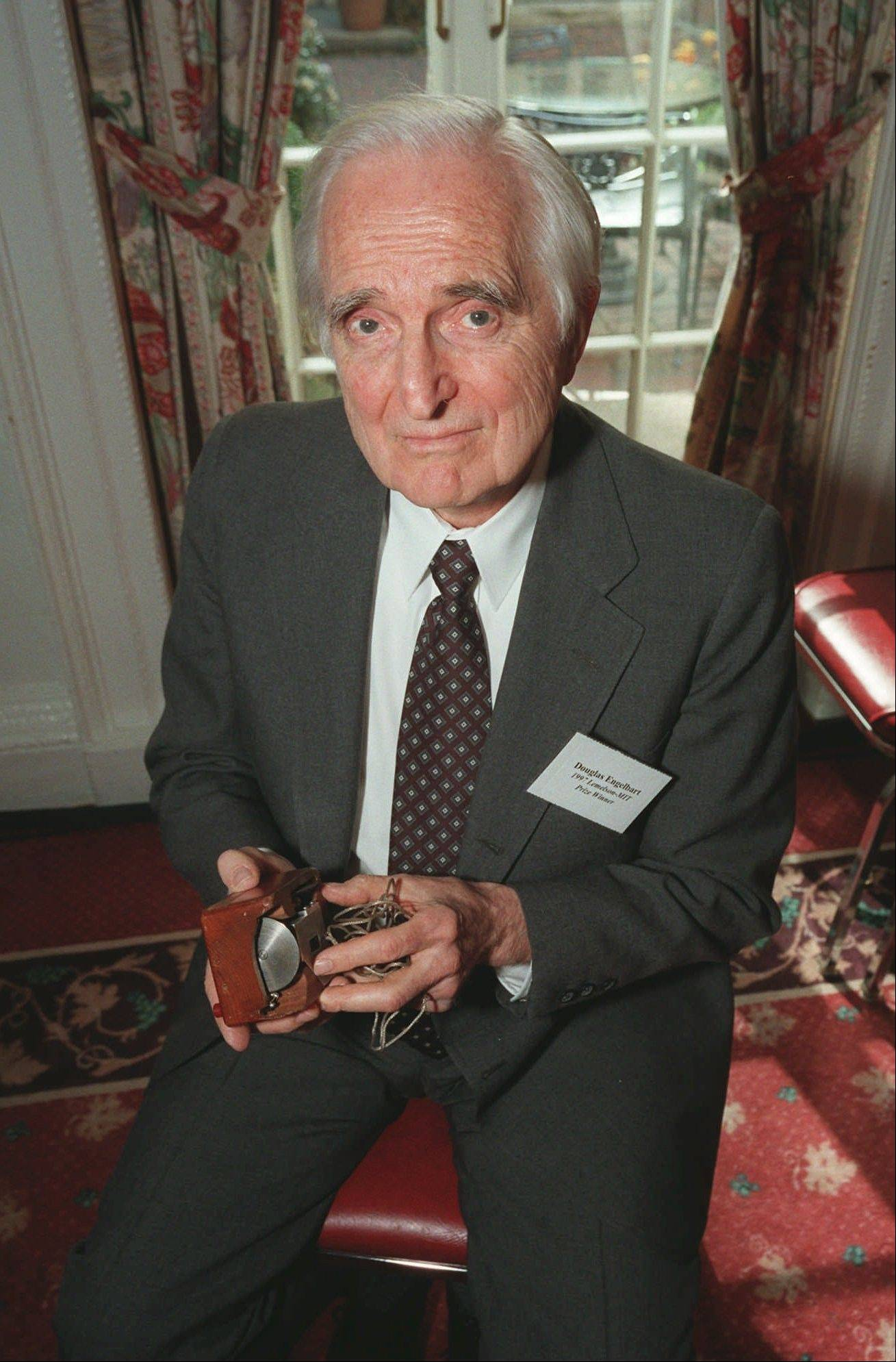 In this April 9, 1997 file photo, Doug Engelbart, inventor of the computer mouse and winner of the half-million dollar 1997 Lemelson-MIT prize, poses with the computer mouse he designed, in New York. Engelbart has died at the age of 88.