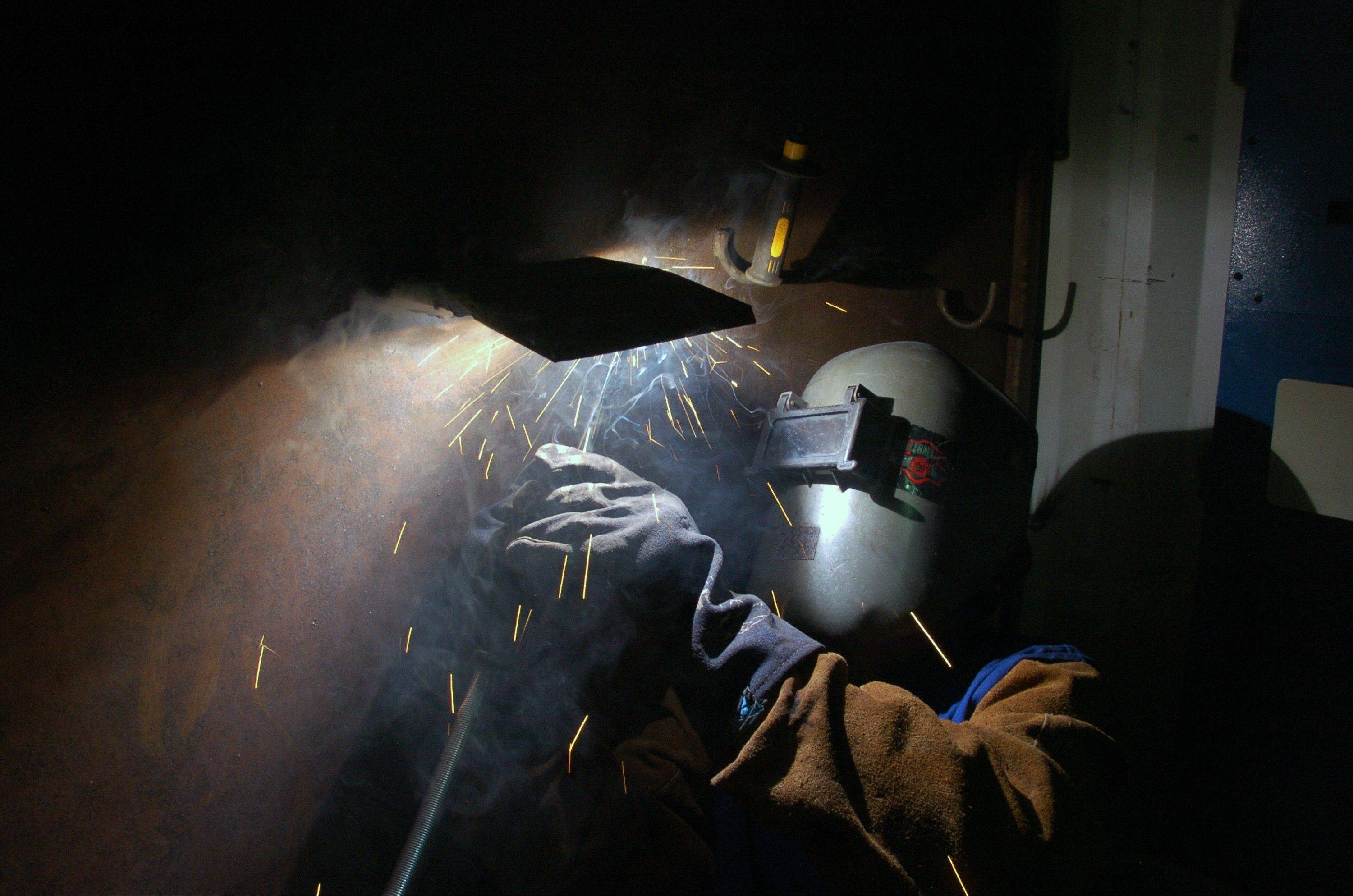 Josh Shomate, an apprentice with the Boilermakers union, works on a weld as part of his training to work at a coal-fired power plant Monday, July 1, 2013, in Colstrip, Mont. Shomate says he quit a job with the U.S. Forest Service to pursue a career in the coal industry.