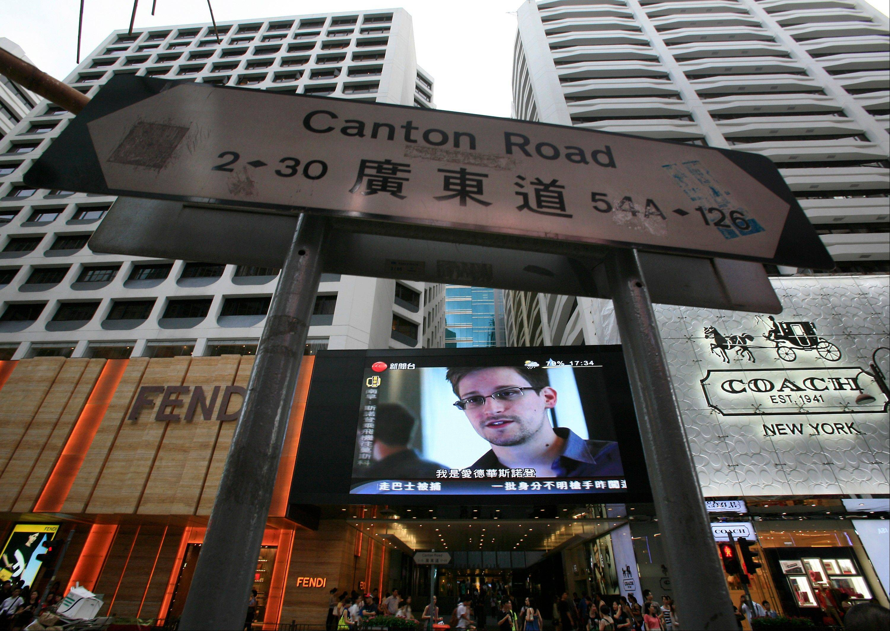 In this June 23, 2013 file photo, a television screen shows a news report of Edward Snowden, a former CIA employee who leaked top-secret documents about sweeping U.S. surveillance programs, at a shopping mall in Hong Kong.