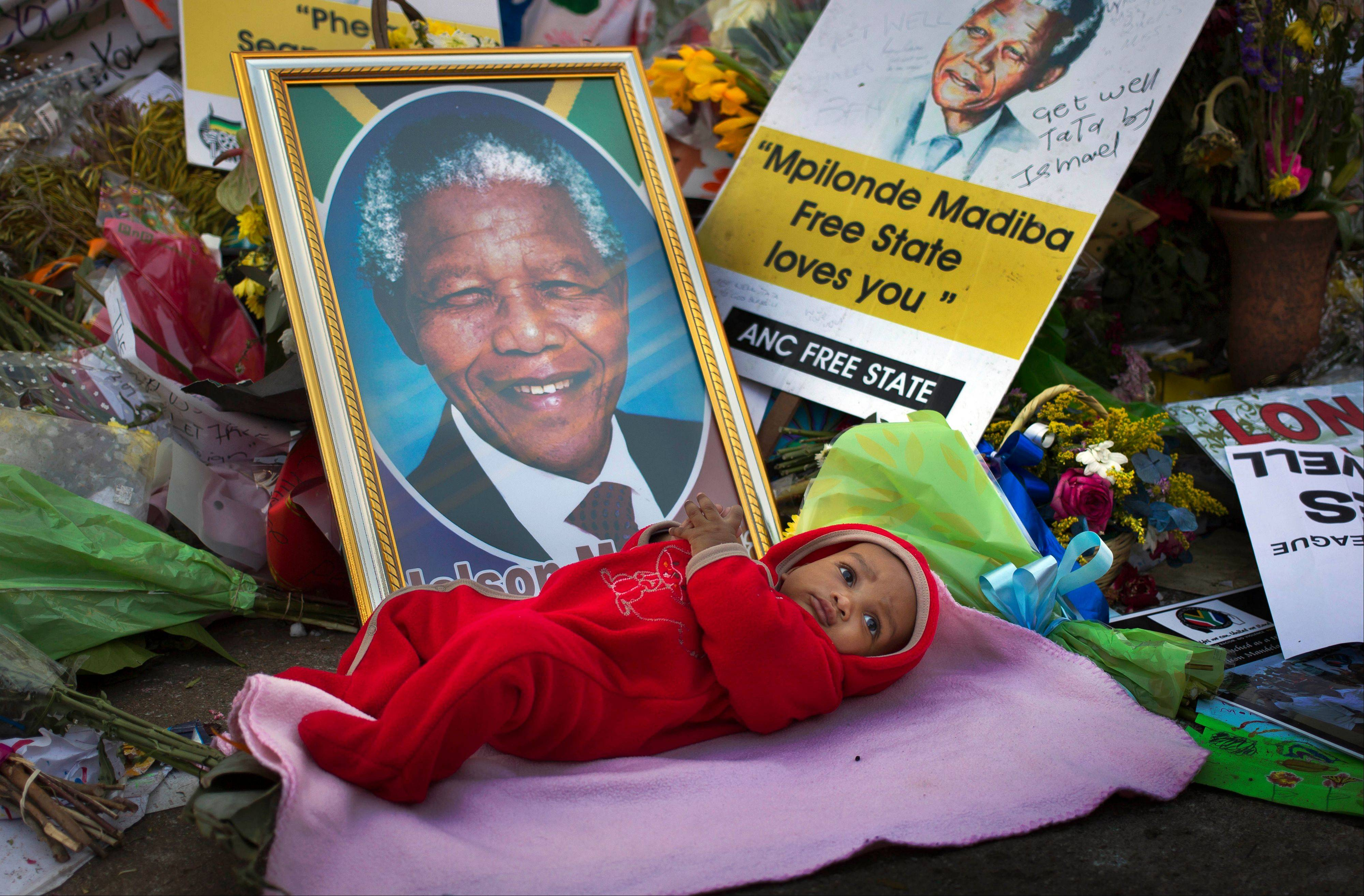 Oamohetswe Mabitsela, 4 months old, is placed by his mother next to a picture of Nelson Mandela for her to take a photograph of him with her camera phone, outside the Mediclinic Heart Hospital where former South African President Nelson Mandela is being treated in Pretoria, South Africa Thursday.