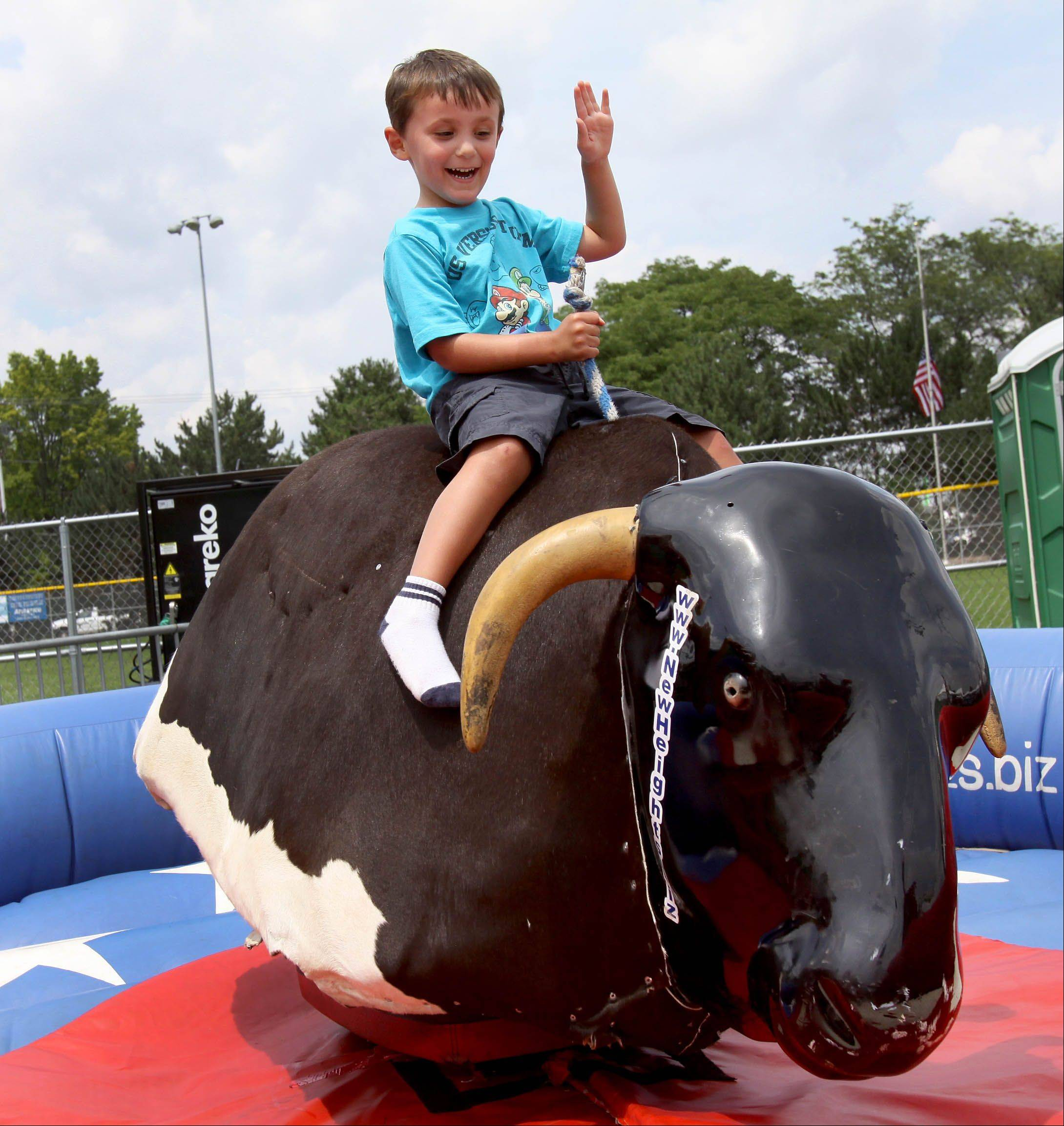 Jake Wittman, 4 of Naperville, takes a ride on the Newhieghts Mechanical Bull, one of the activities at Ribfest in Naperville on Thursday.
