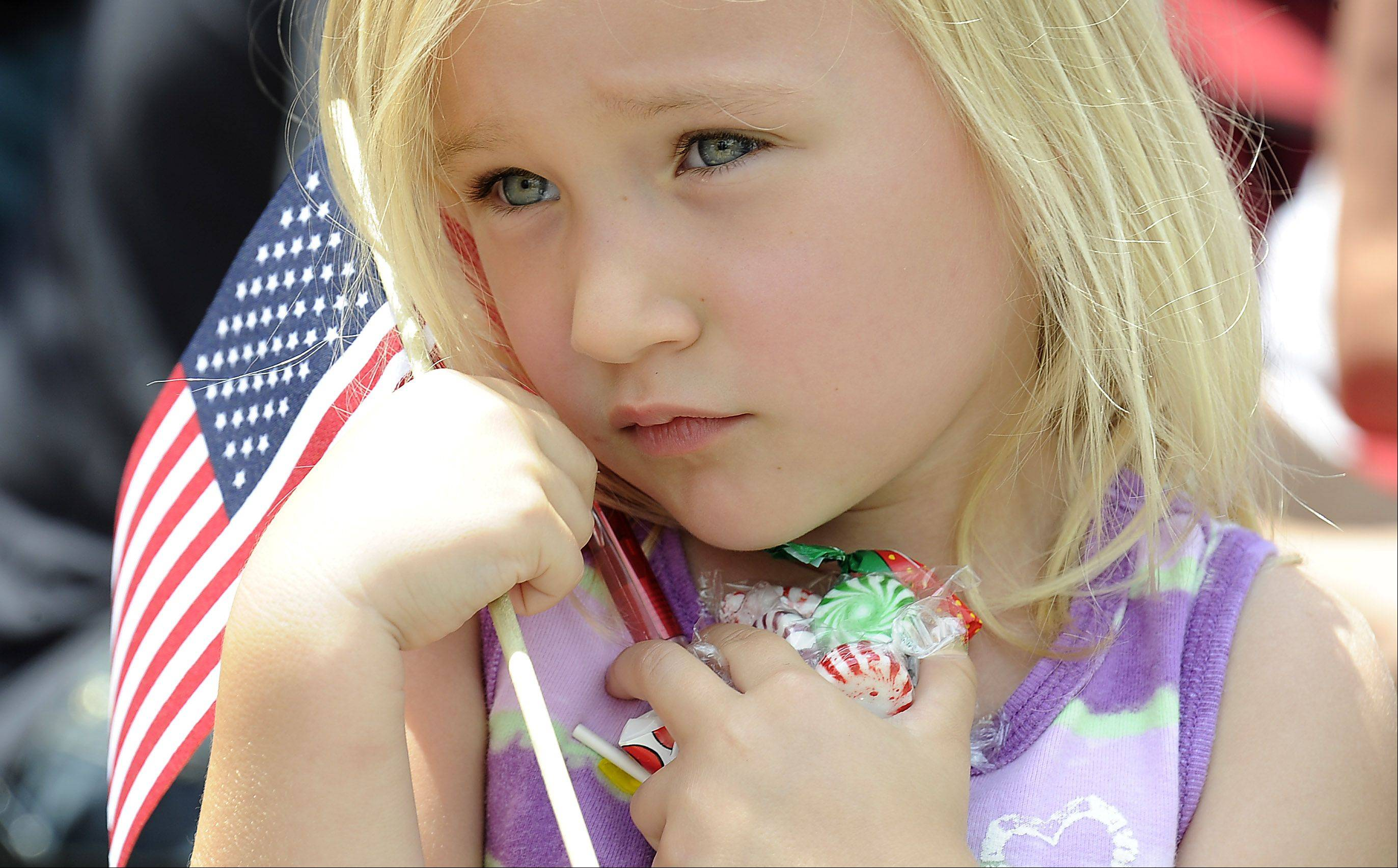 Mt. Prospect July Fourth festivities has Veronica Wrona, 5, of Mt. Prospect protecting her candy stash and holding the colors as she watches the parade roll by.