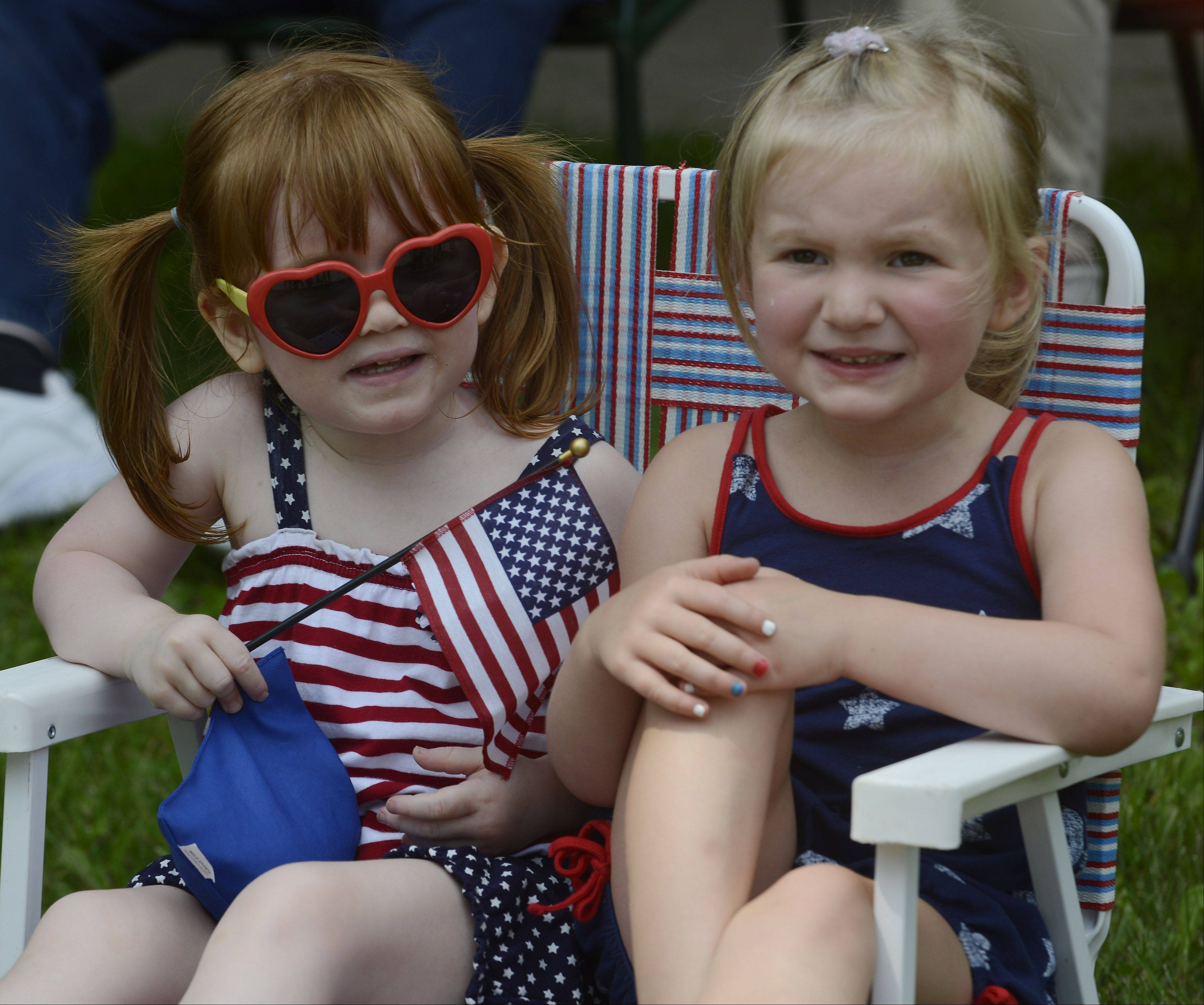 Cousins Grace Carroll, 2, left, and Megan Murray, 3, both of Rolling Meadows, sit together during the Rolling Meadows Fourth of July parade Thursday.