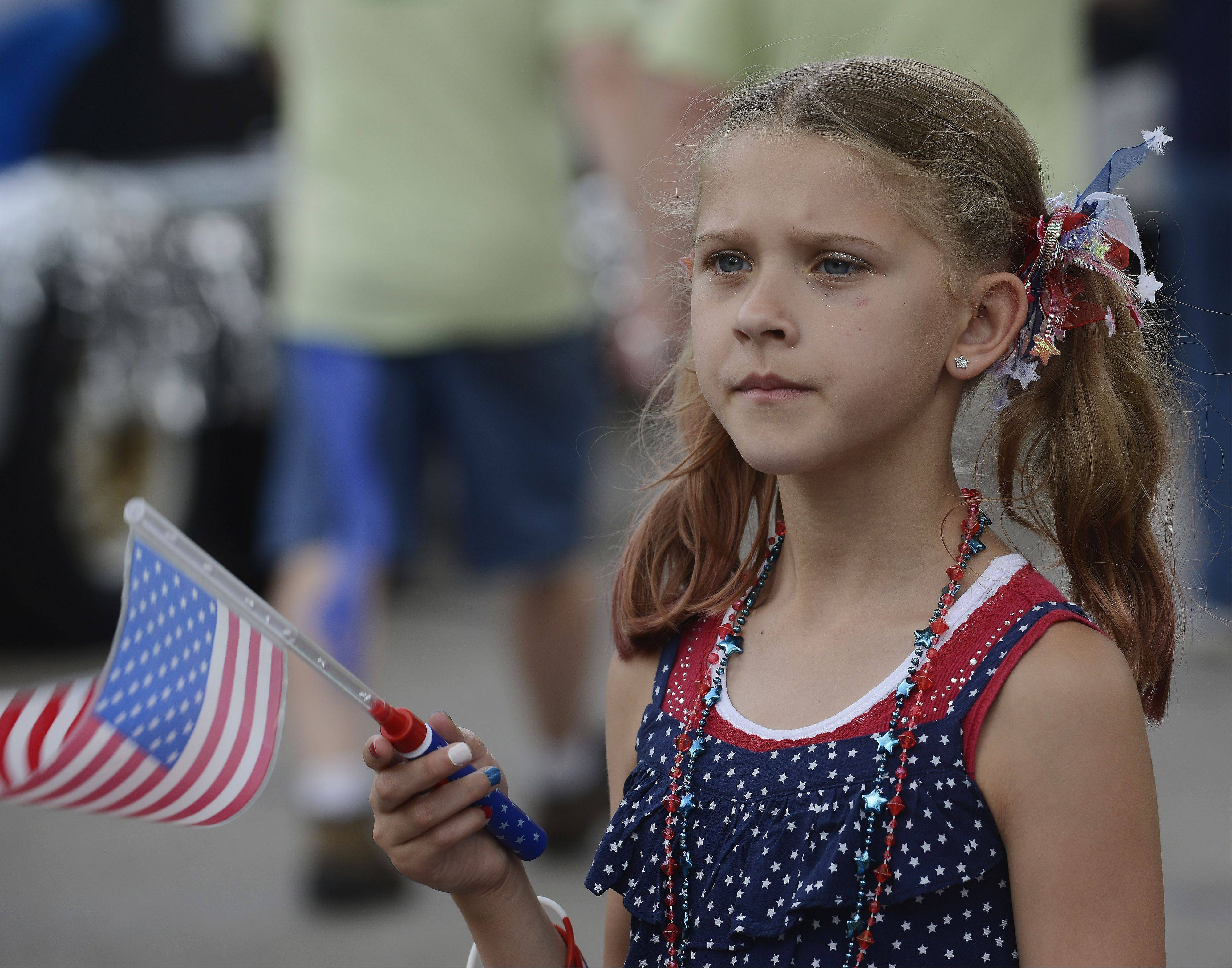 Lily Worline, 9, of Crystal Lake waves her flag during the Rolling Meadows Fourth of July parade Thursday.