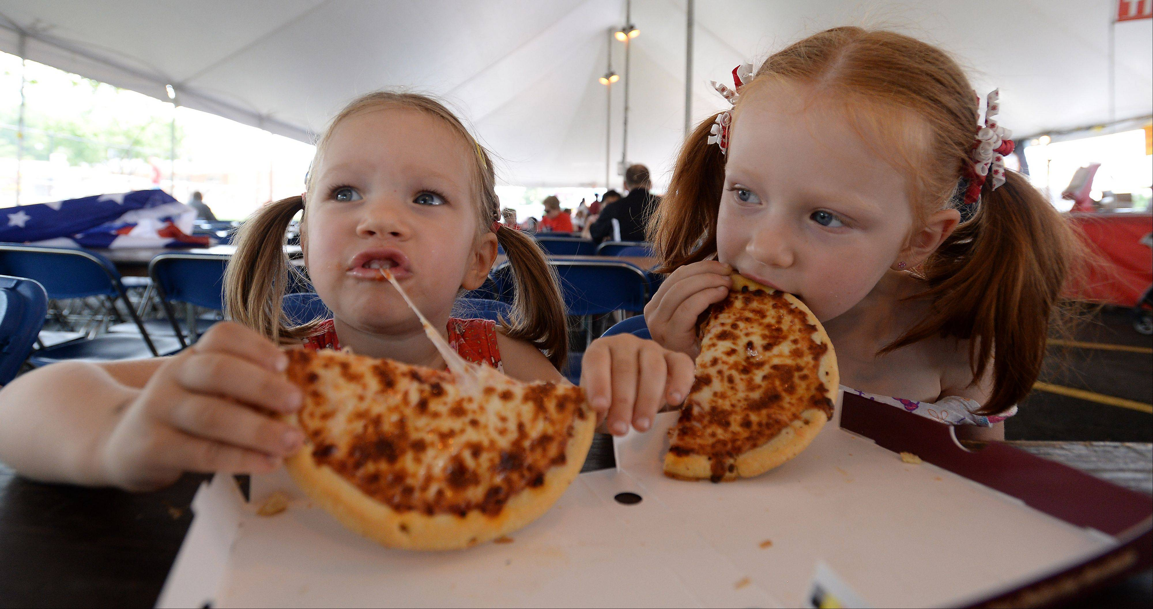 Frontier Days festivities kicks off on the Fourth of July with Nela, 3, and her sister Ula Zadecki, 5, of Arlington Heights finding the pizza hot and cheesy as they have lunch after the parade.