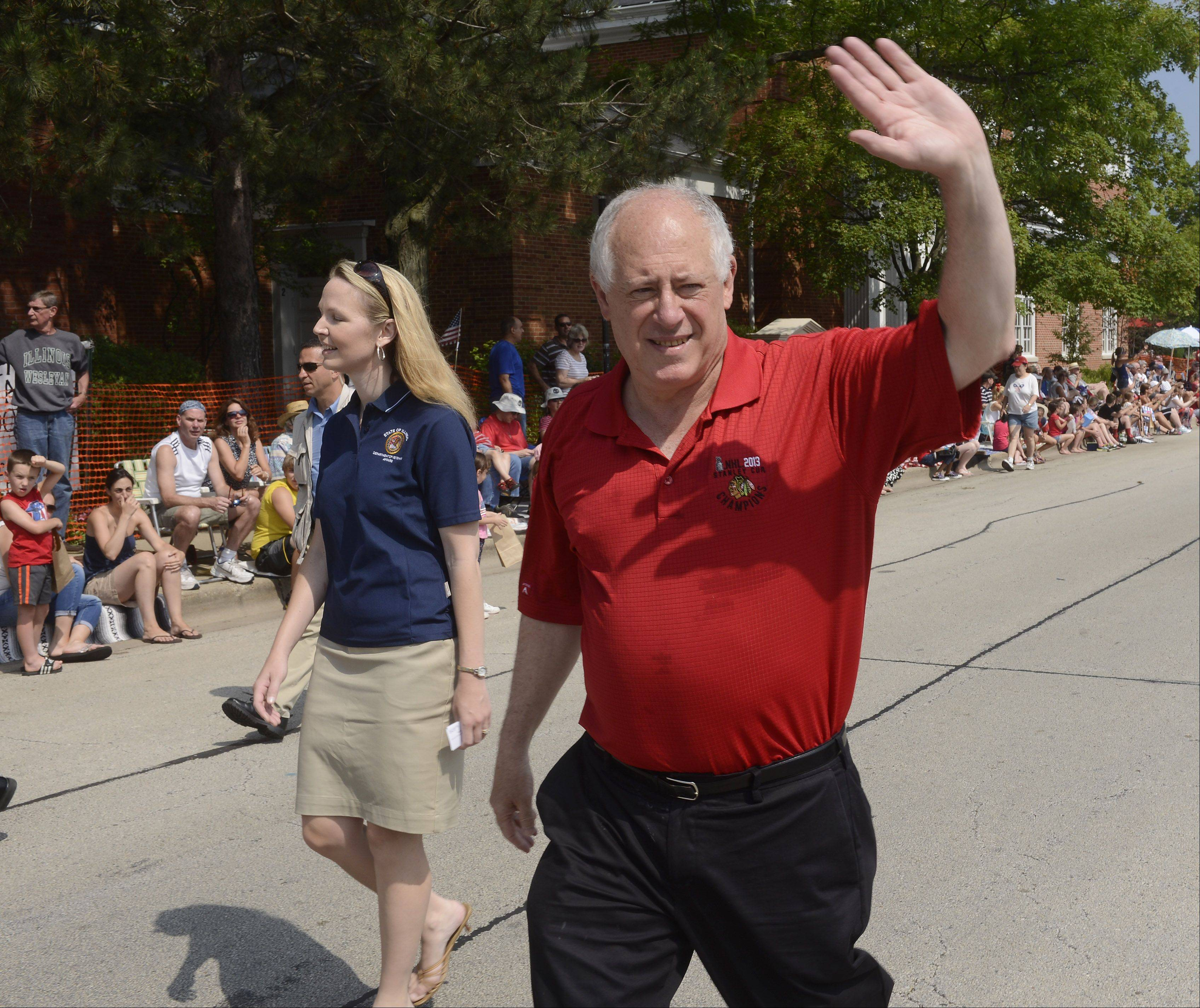 Illinois Governor Pat Quinn waves to the crowd while marching in the Arlington Heights Fourth of July parade Thursday.