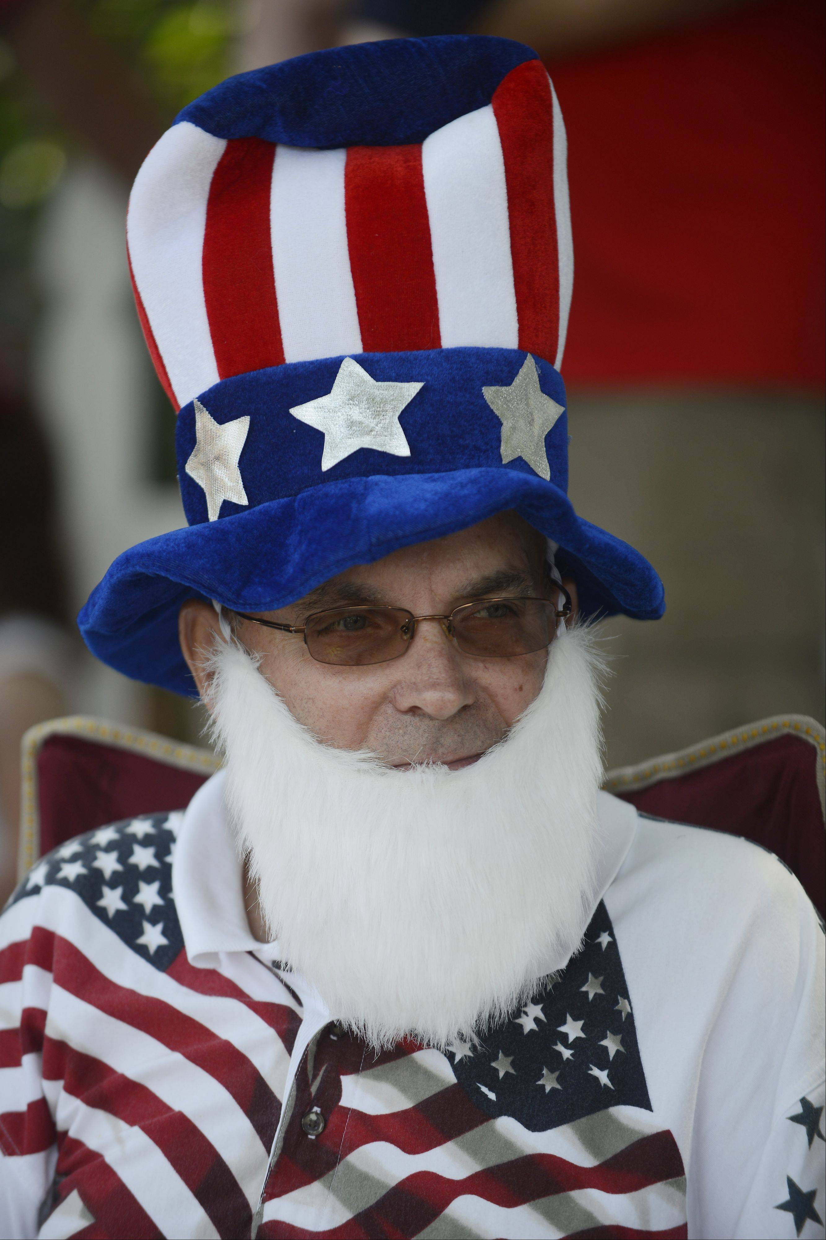 Jim Grzenia of Arlington Heights wears and Uncle Sam hat and beard while watching the Arlington Heights Fourth of July parade Thursday.