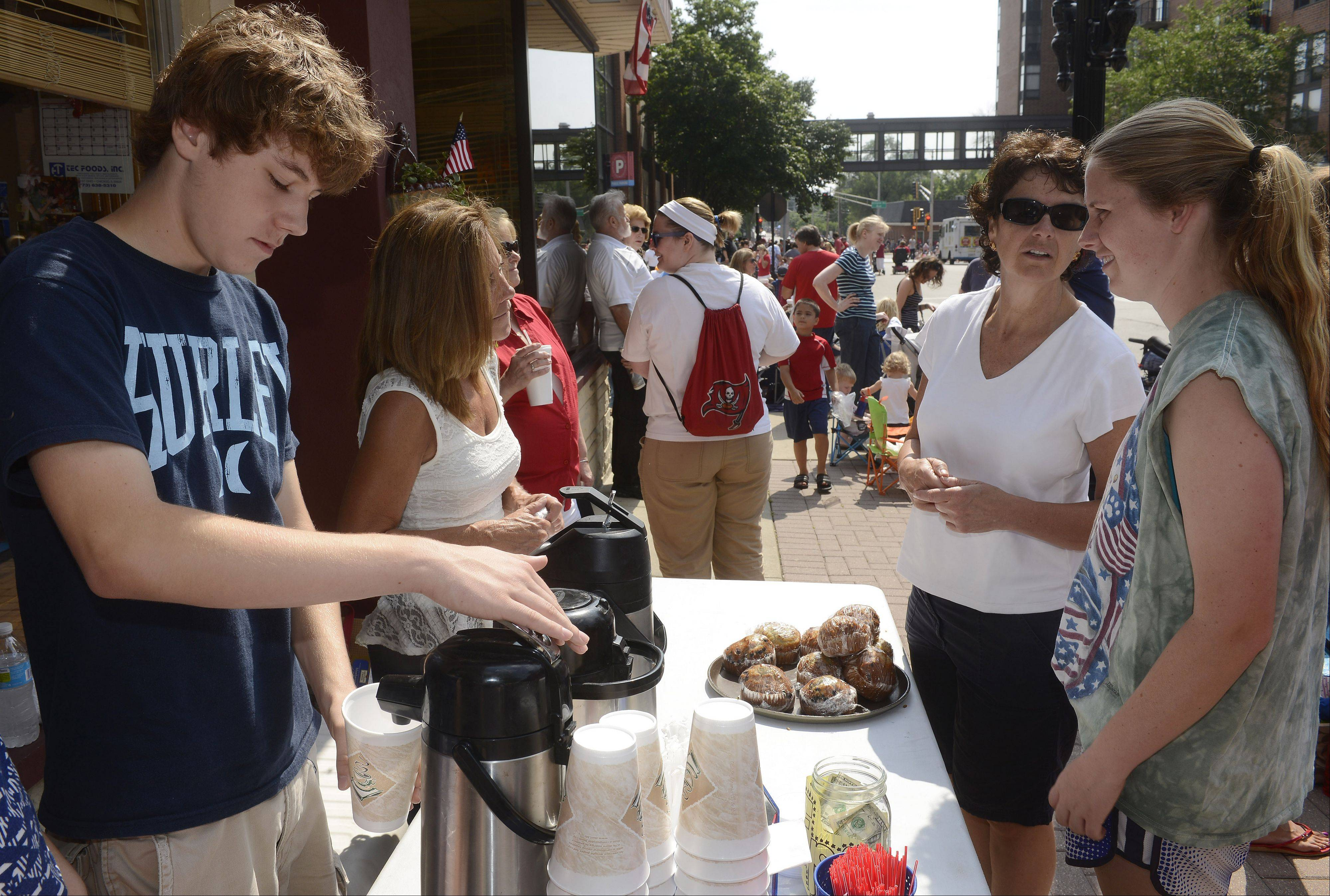 Logan Boven of Arlington Heights pours a cup of coffee as he and his mom, Vicki, serve Anna Walsh, second from right, and her daughter Colleen Clark, both of Arlington Heights, outside the Uptown Cafe prior to the Arlington Heights Fourth of July parade Thursday.