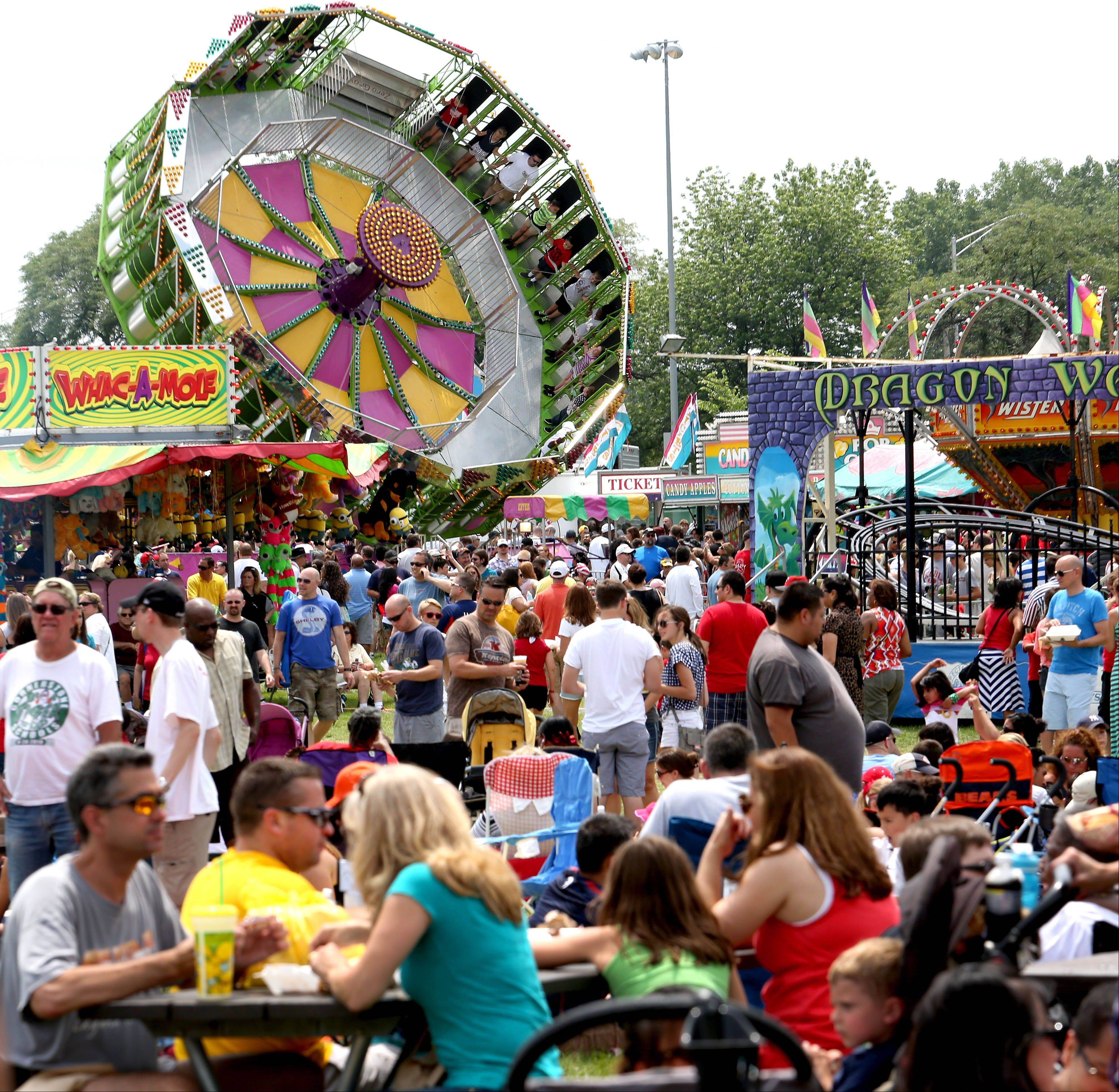Crowds enjoy ribs, music and carnival rides during Ribfest in Naperville on Thursday.