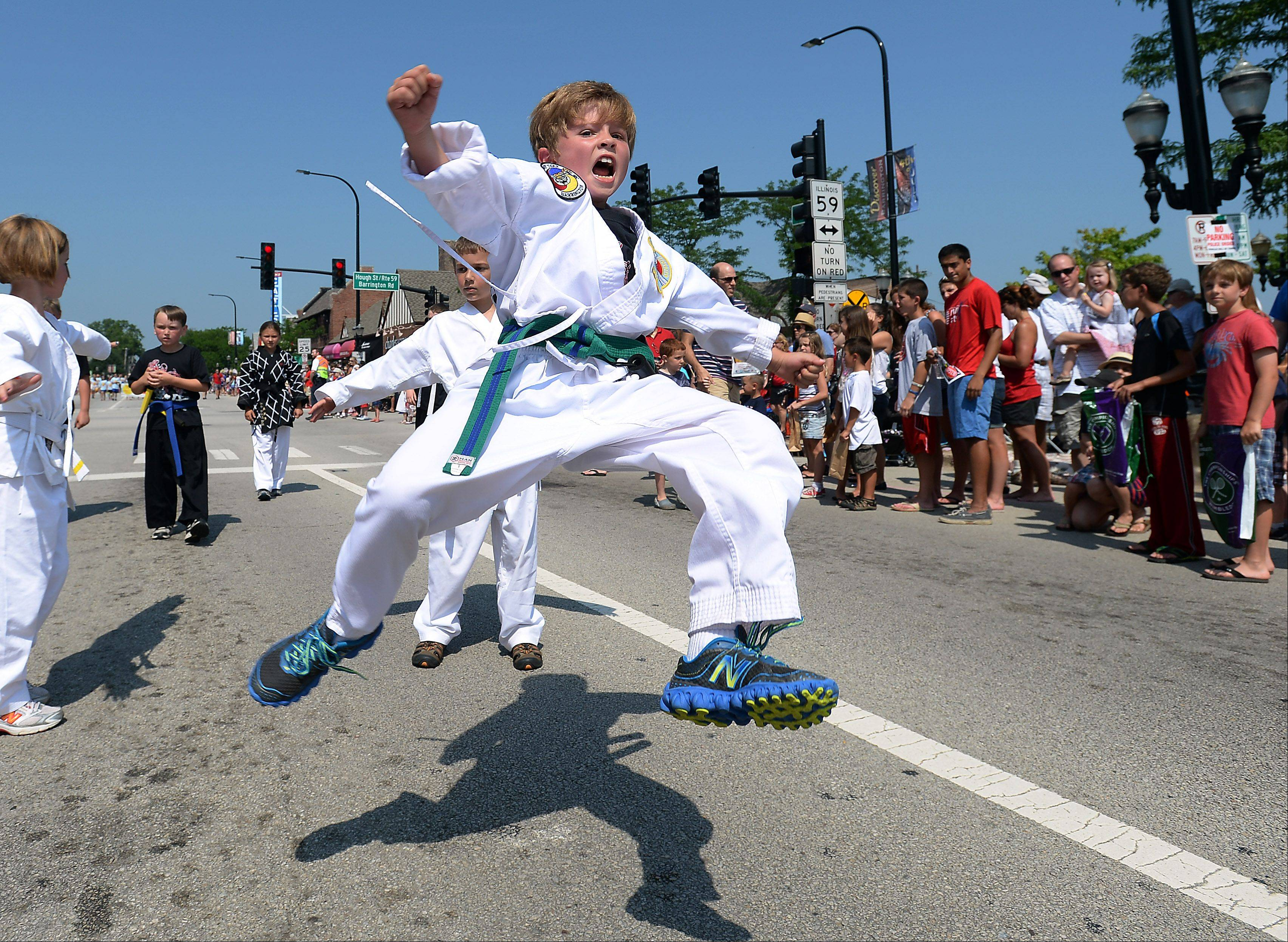 Barrington's Fourth of July parade kicks off downtown with Ryan Devona, 8, of Barrington kicking it down the parade route as part of their Tiger Martial Arts.