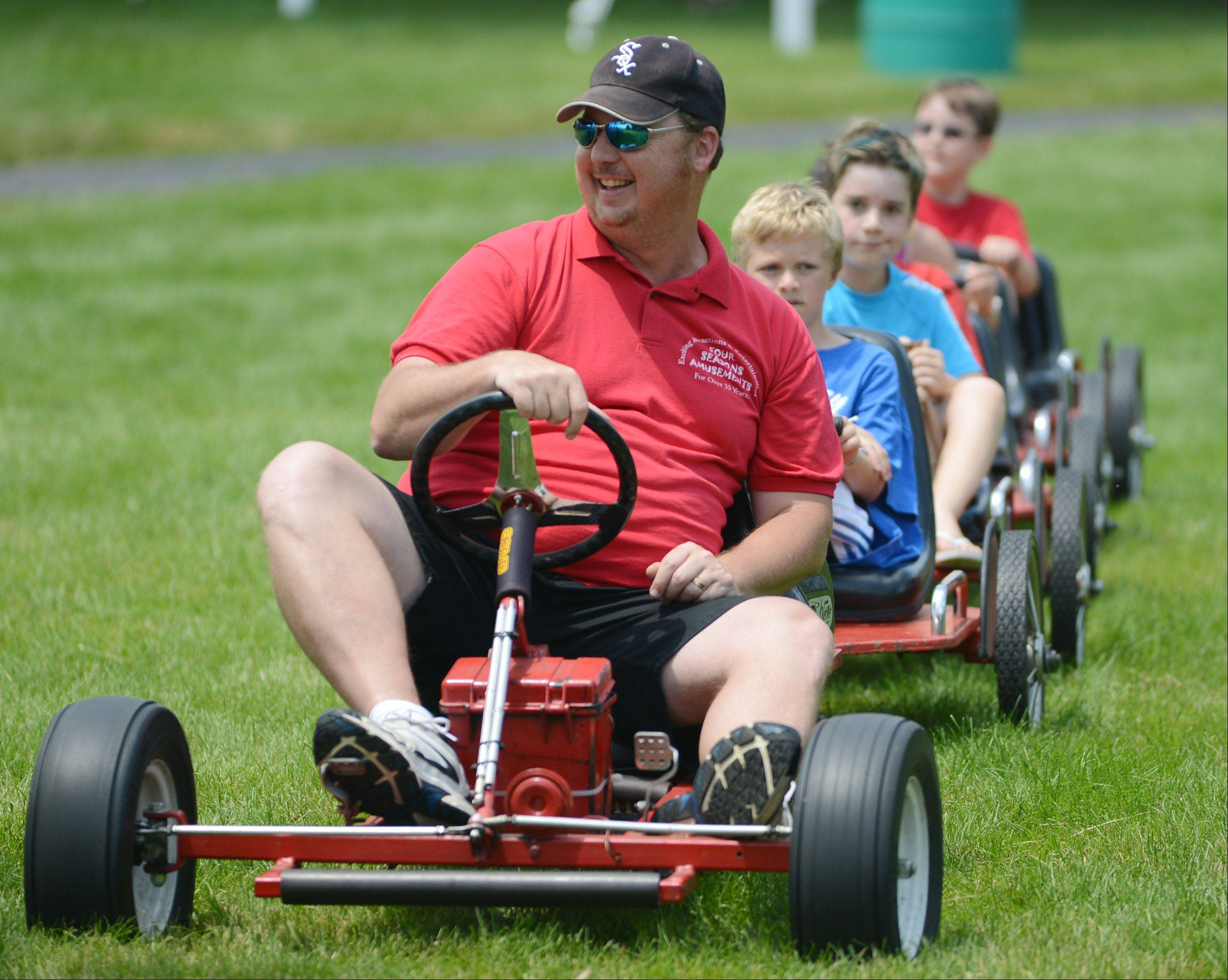 Erik Sundling of Four Seasons Amusements gives train rides to kids during Lake Zurich's Fourth of July celebration in Paulus Park on Thursday.