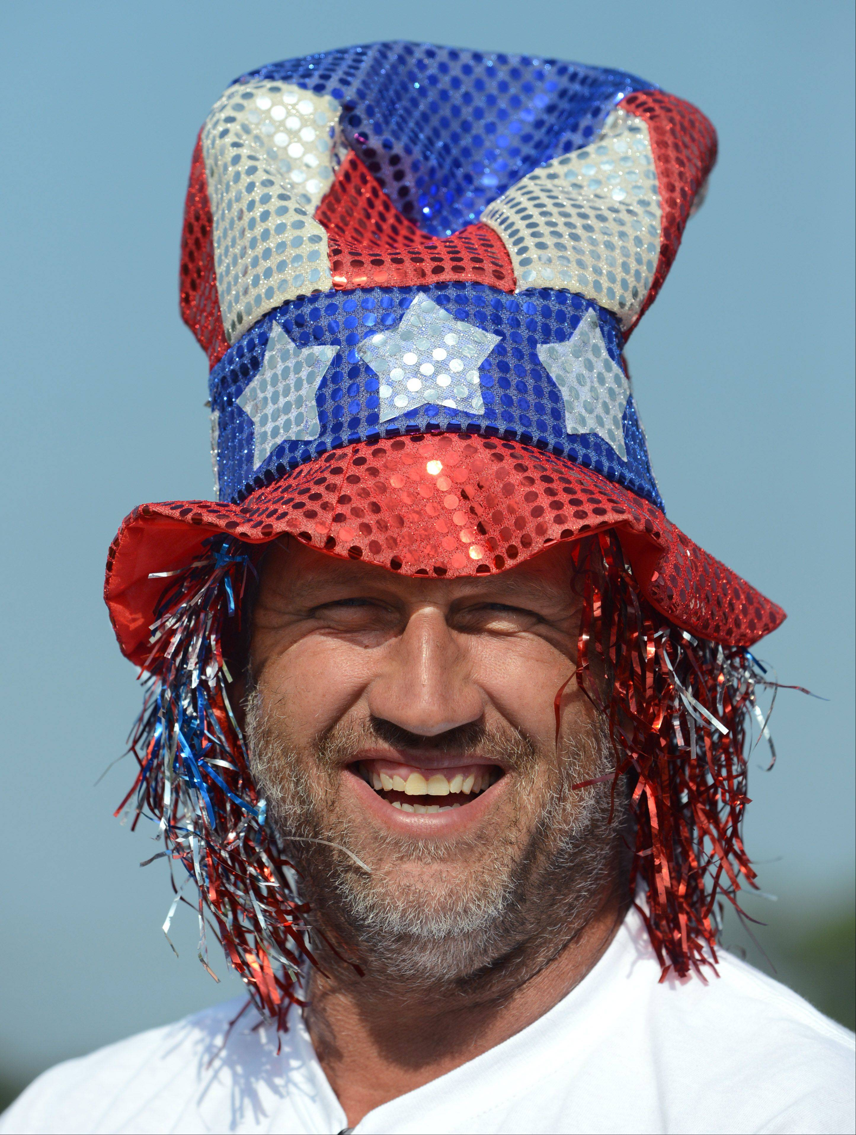 Arnie Poppe of Spring Grove shows of his colors as he drives the float for Krueger's Farm during Thursday's Fourth of July parade in Lakemoor.