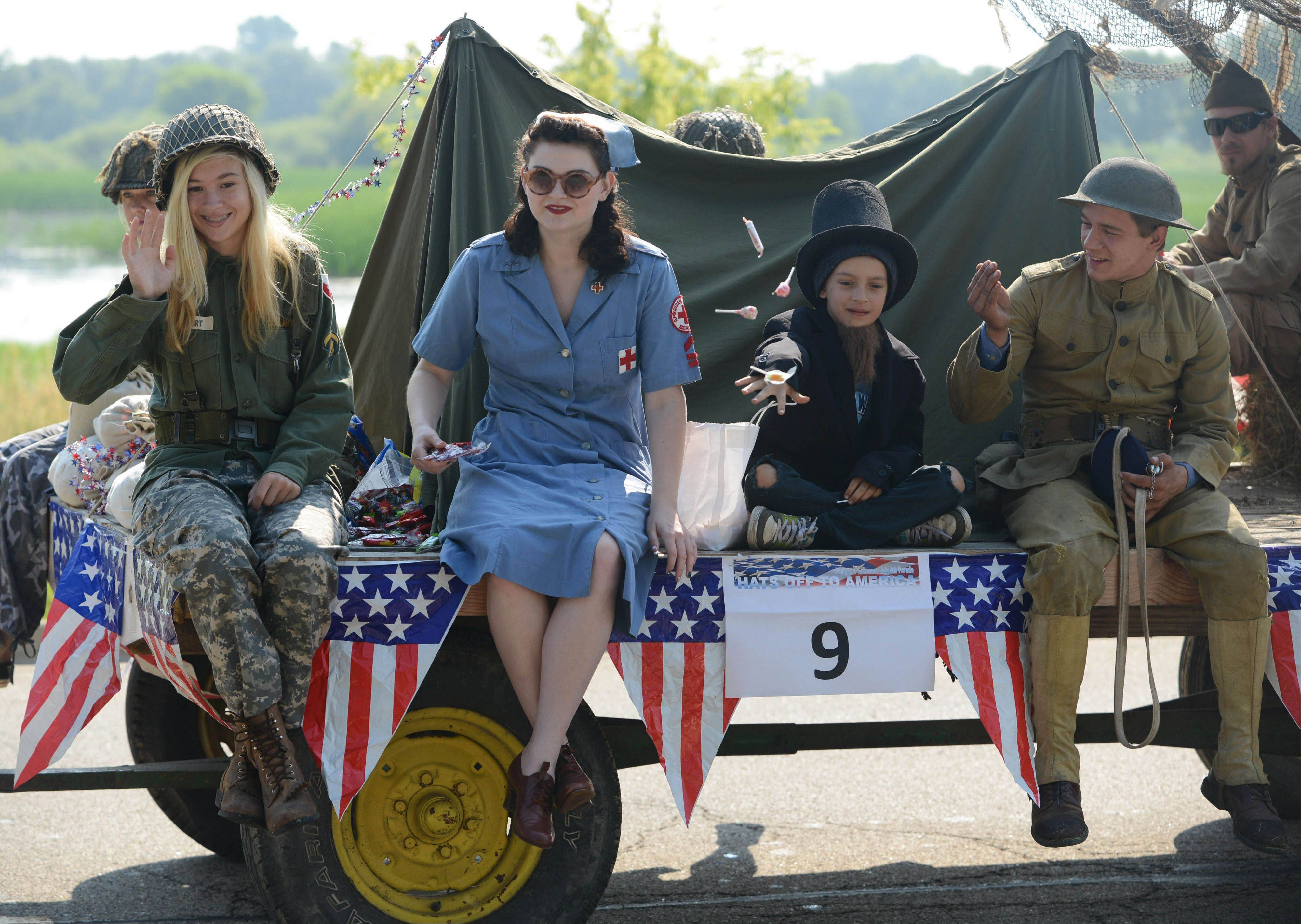 Arei Bein, from left, Julia Fisher, Payton Johnson and Sam Johnson throw candy from the Johnson family's military themed float during Thursday's Fourth of July parade in Lakemoor.