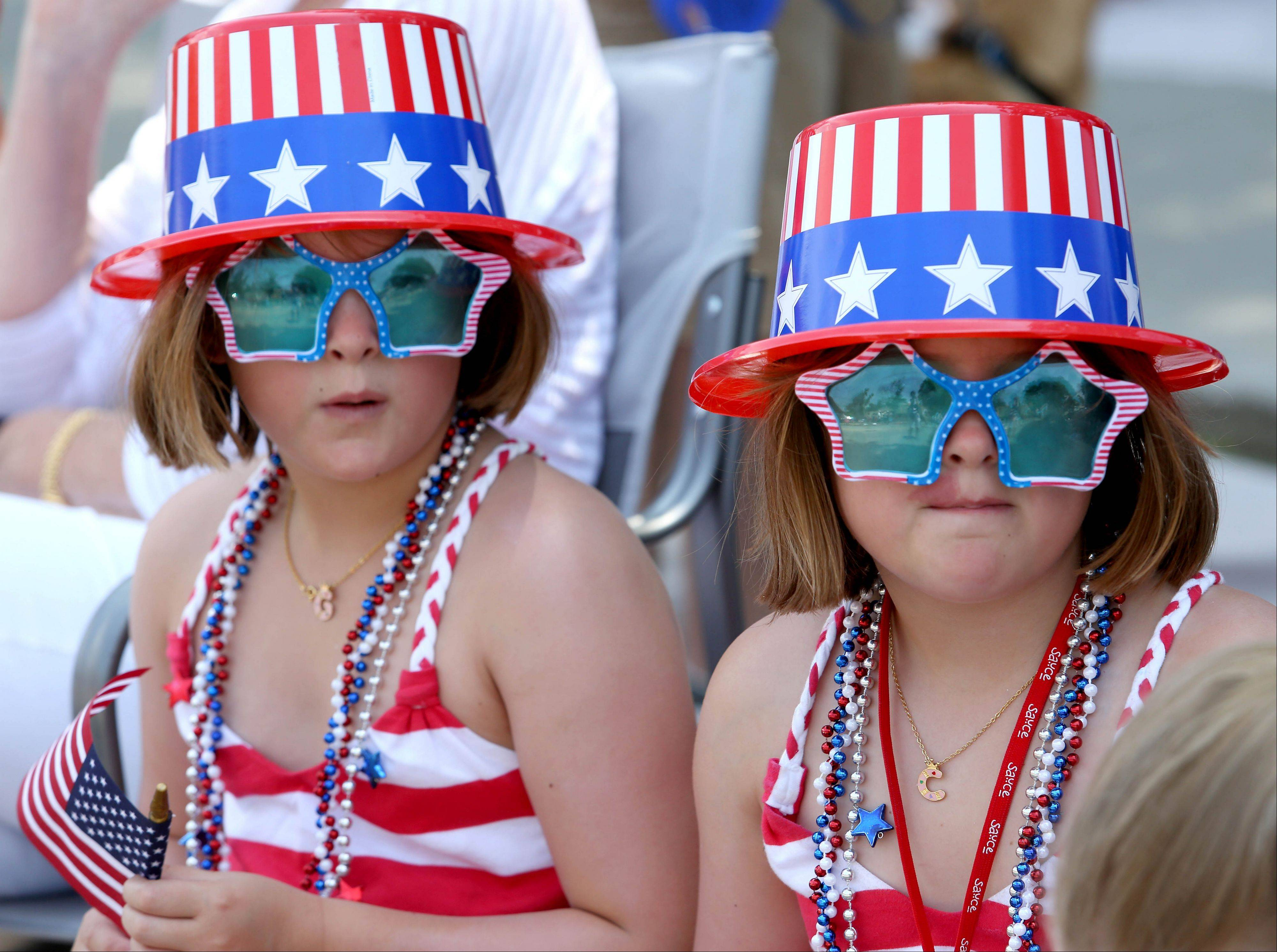 Twins Grace, left and Catherine Cahill, right, are decked out in patriotic wear as they wait for the 4th of July parade in Glen Ellyn on Thursday.