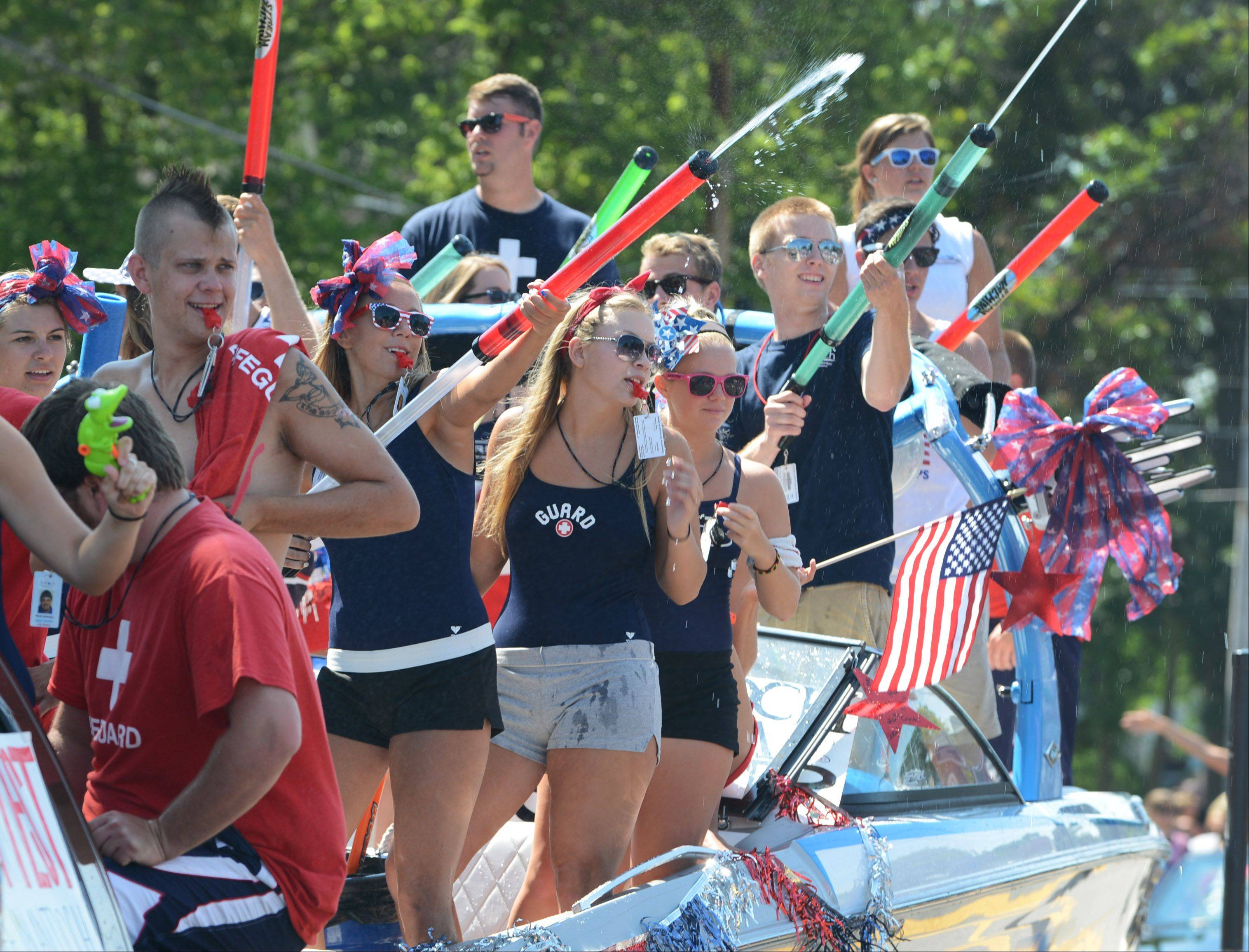 Life guards from the Antioch Aqua Center spray parade-goers along Main Street Thursday morning during Antioch's Fourth of July parade.