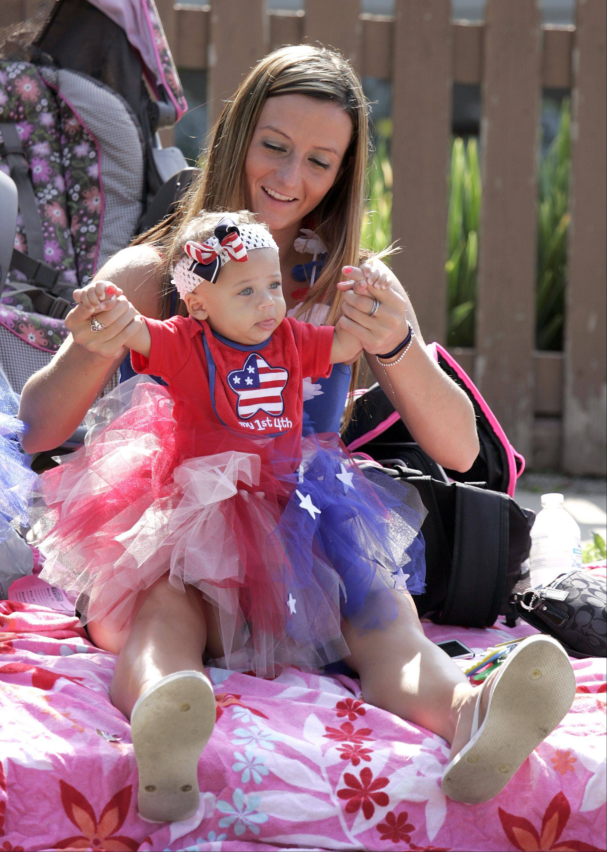 Six-month-old Sierra Luellen gets some help dancing from her mom Sarah Carigan during the Elgin Fourth of July Parade Thursday.
