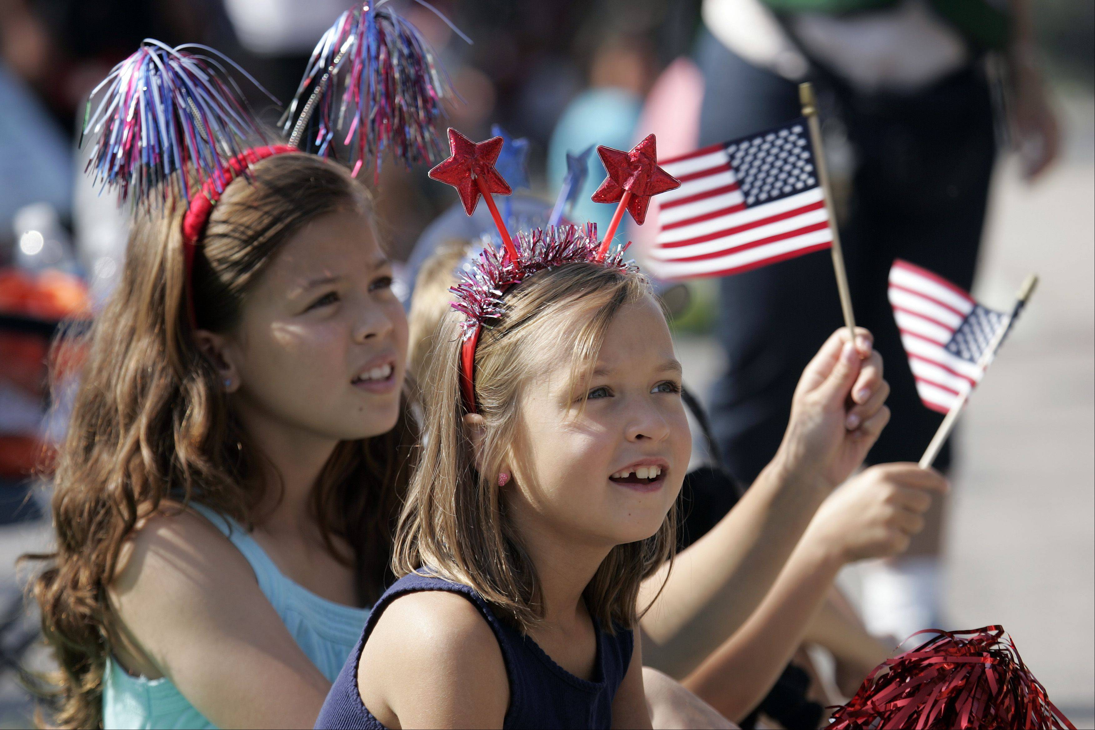 Mya Chan, 10, of Huntley, left, and Abigail Ludwig, 8, of Elgin get a good look at the floats during the Elgin Fourth of July Parade Thursday.