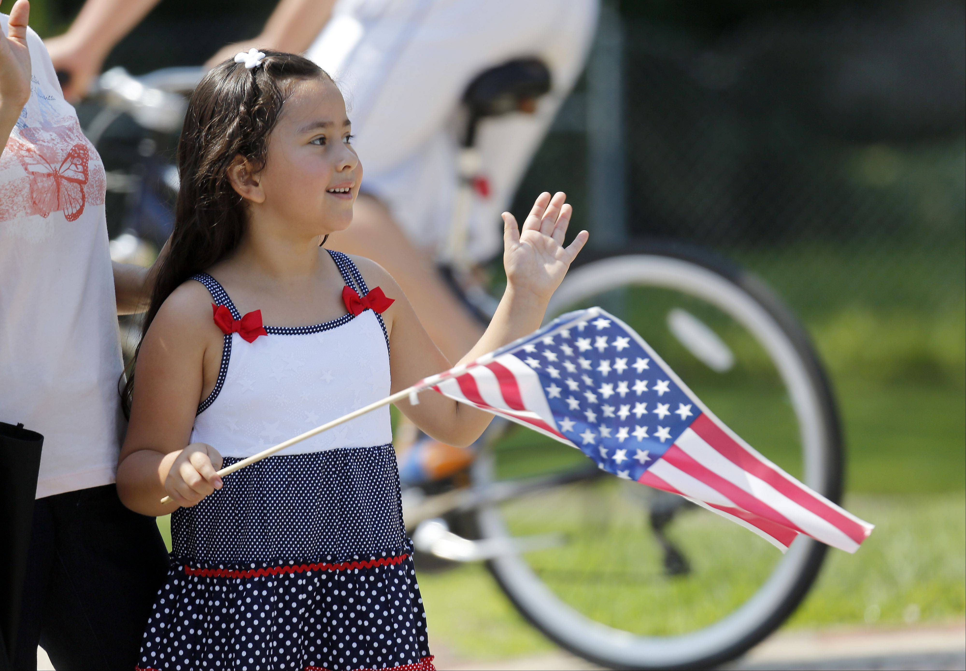 Six-year-old Isabella Diaz of South Elgin waves her flag during the South Elgin Fourth of July Parade Thursday.